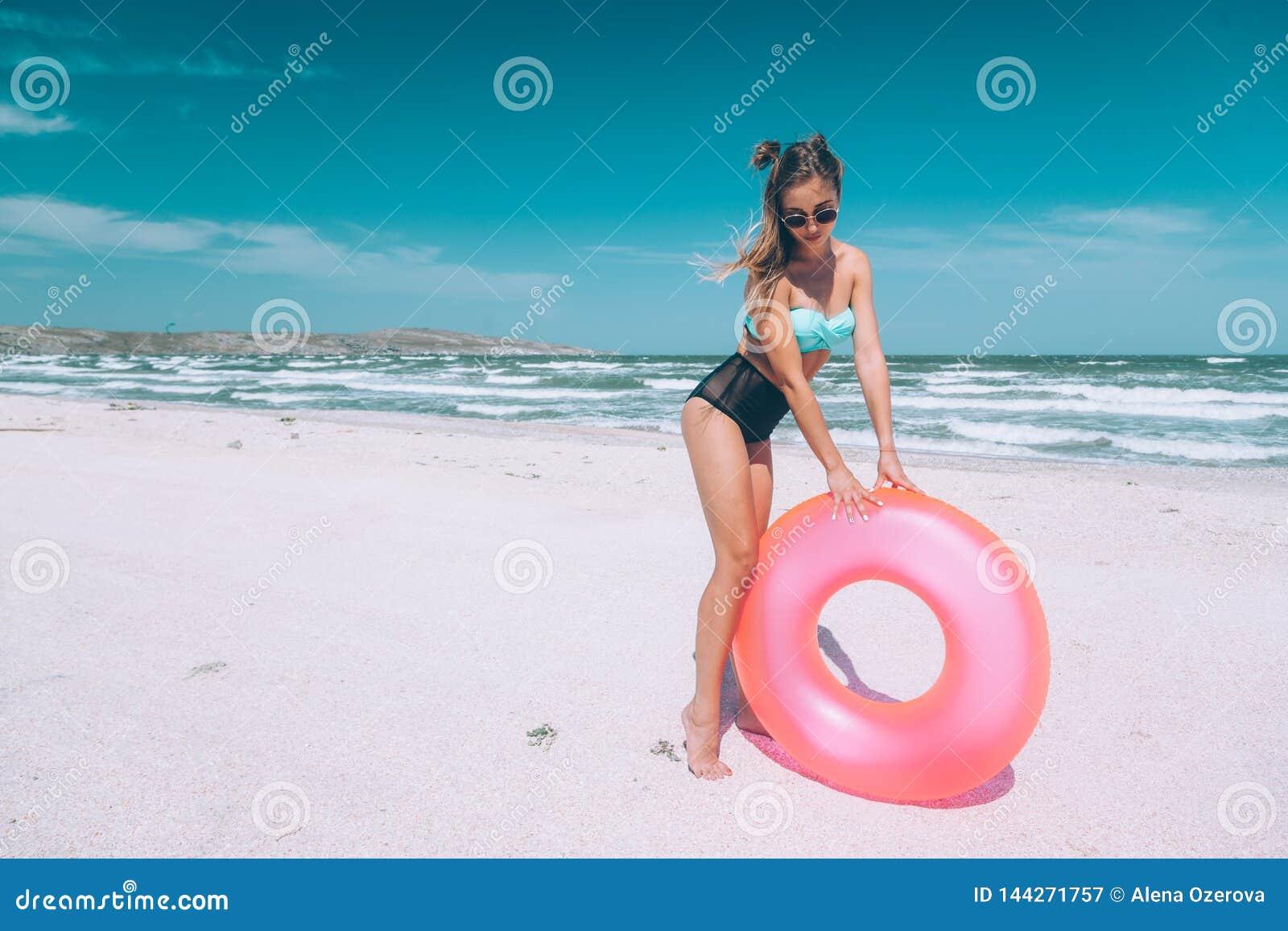 Χαλάρωση κοριτσιών στο ρόδινο lilo στην παραλία