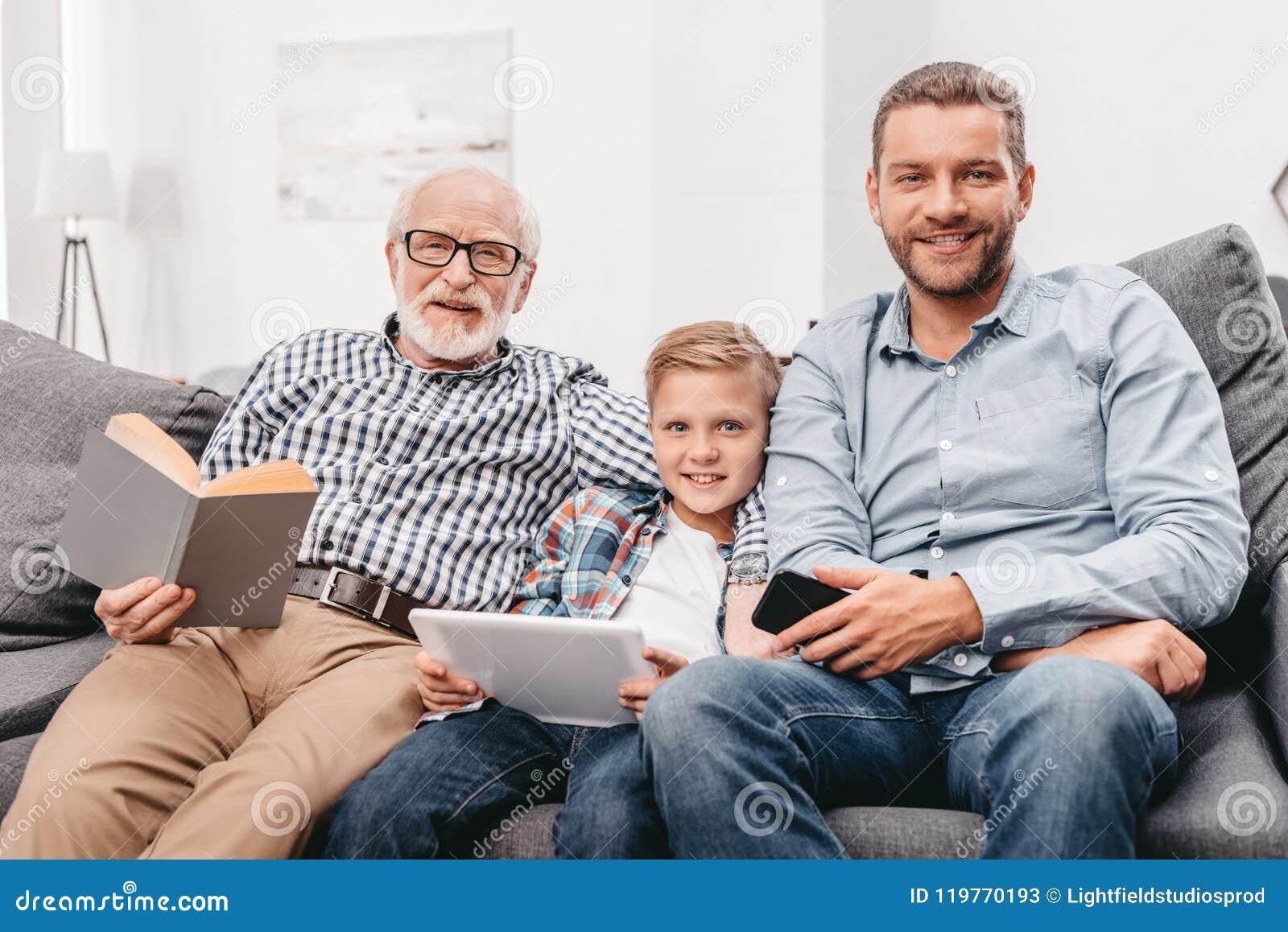 Χαλάρωση πατέρων, γιων και παππούδων μαζί στον καναπέ στο καθιστικό με την ψηφιακή ταμπλέτα, smartphone