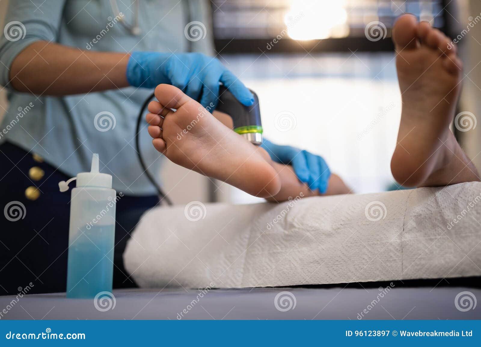Χαμηλό τμήμα του αγοριού που λαμβάνει την ανίχνευση υπερήχου στα πόδια από το θηλυκό φυσιοθεραπευτή