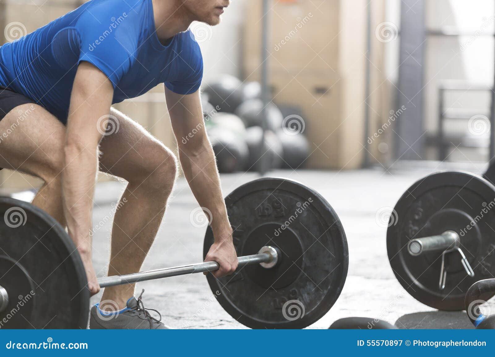 Χαμηλό τμήμα του αφιερωμένου ατόμου που ανυψώνει barbell στη γυμναστική crossfit