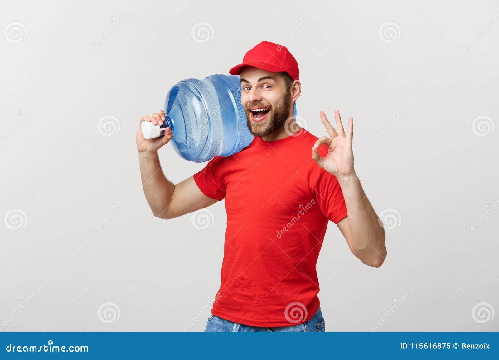 Χαμογελώντας αγγελιαφόρος παράδοσης εμφιαλωμένου νερού πορτρέτου στην κόκκινη μπλούζα και τη φέρνοντας δεξαμενή ΚΑΠ του χυμού και