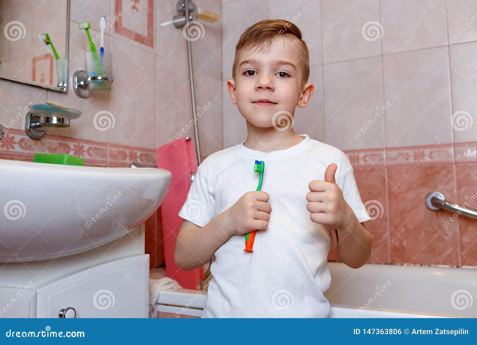 Χαμογελώντας αγόρι που στέκεται στο λουτρό με την οδοντόβουρτσά του και τον αντίχειρά του επάνω Οδοντική έννοια υγιεινής και υγει