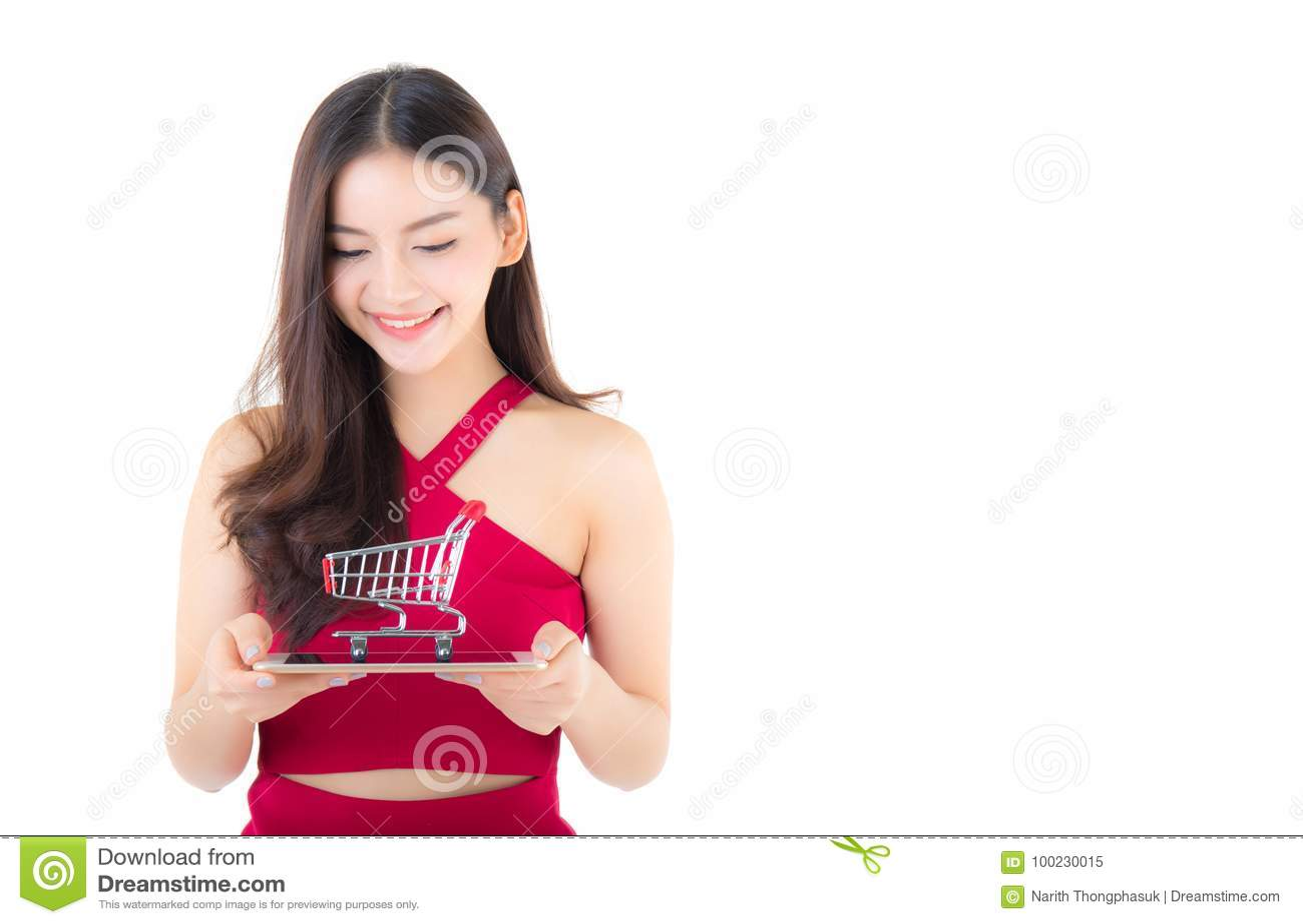 Χαμογελώντας ασιατική γυναίκα στην κόκκινη ταμπλέτα εκμετάλλευσης φορεμάτων με το ευτυχές κορίτσι και κάρρο στην ταμπλέτα