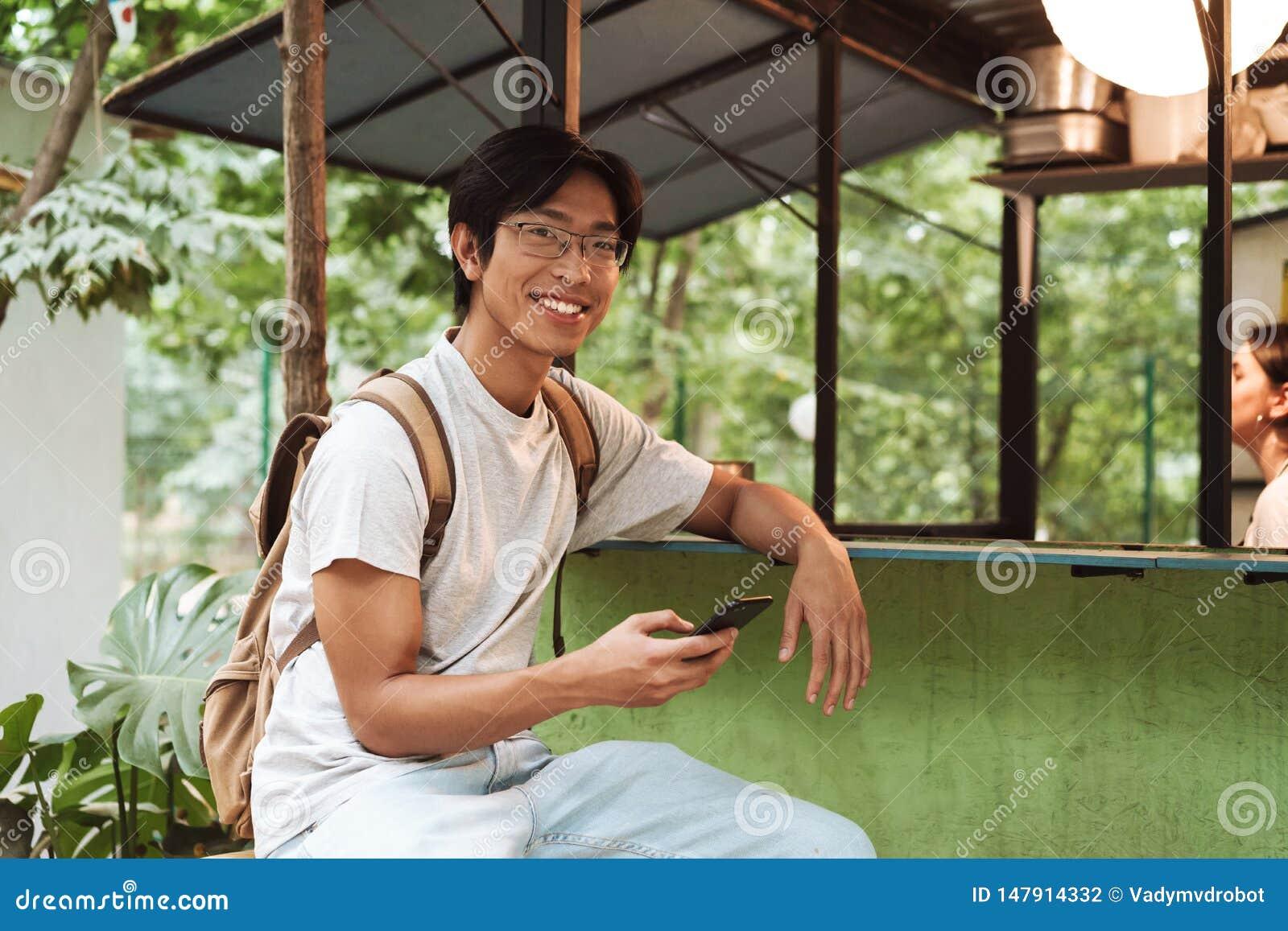 Χαμογελώντας ασιατικό άτομο σπουδαστών που φορά το σακίδιο πλάτης