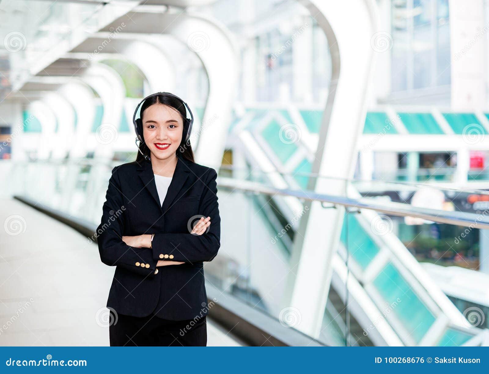 Χαμογελώντας γυναίκα που φορά την κάσκα μικροφώνων ως χειριστή,