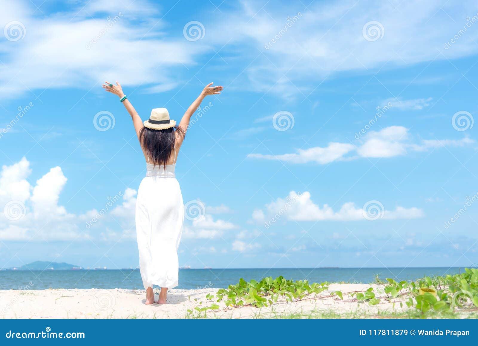 Χαμογελώντας γυναίκα που φορά το άσπρο καλοκαίρι φορεμάτων μόδας που περπατά στην αμμώδη ωκεάνια παραλία, όμορφο υπόβαθρο μπλε ου