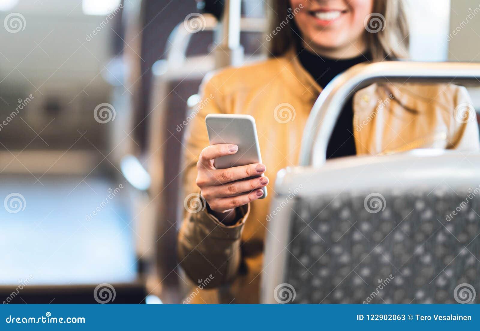 Χαμογελώντας γυναίκα που χρησιμοποιεί το smartphone στο τραίνο, τον υπόγειο, το λεωφορείο ή το τραμ