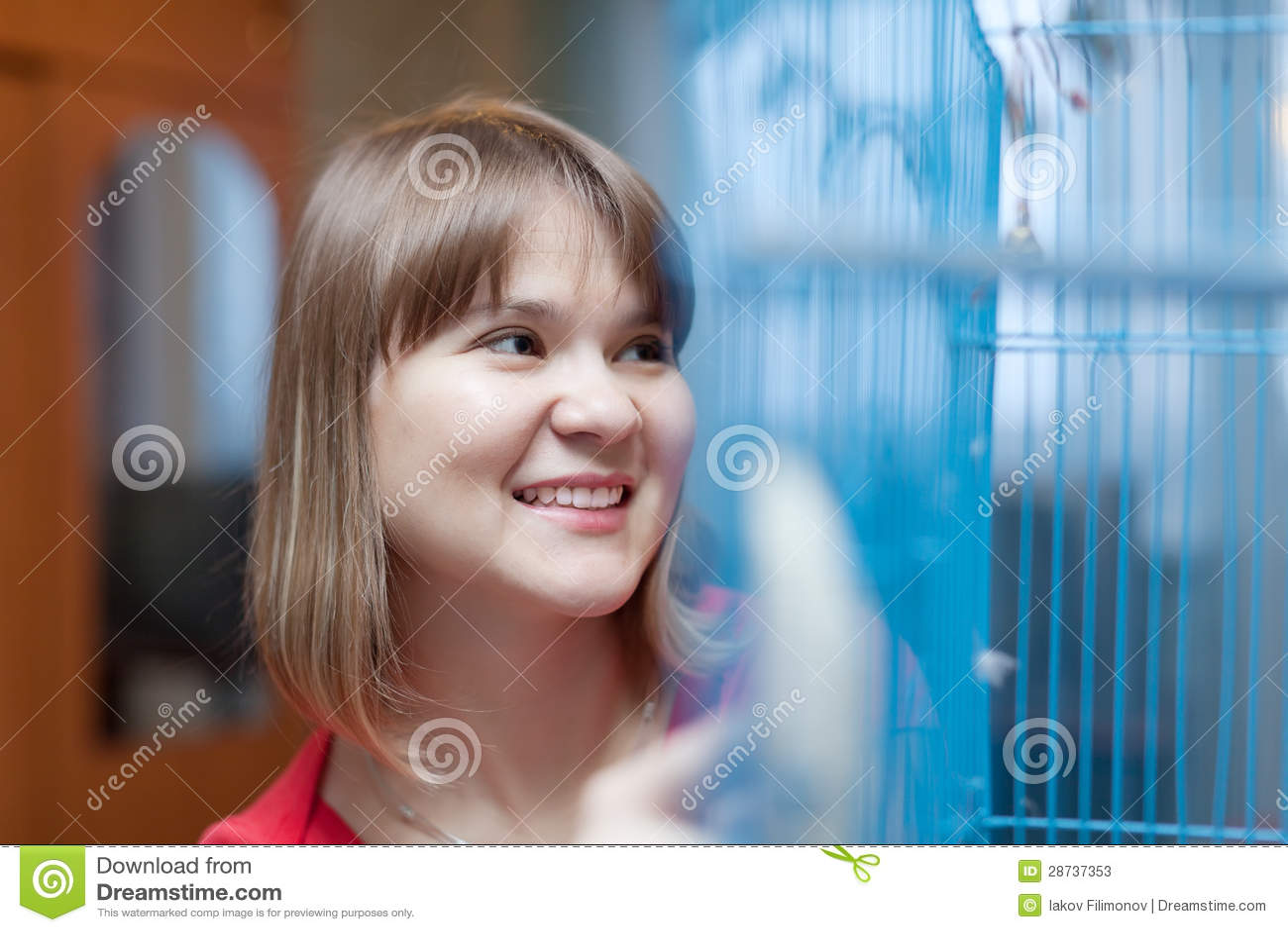 Χαμογελώντας γυναίκα στο κλουβί με τα κατοικίδια ζώα