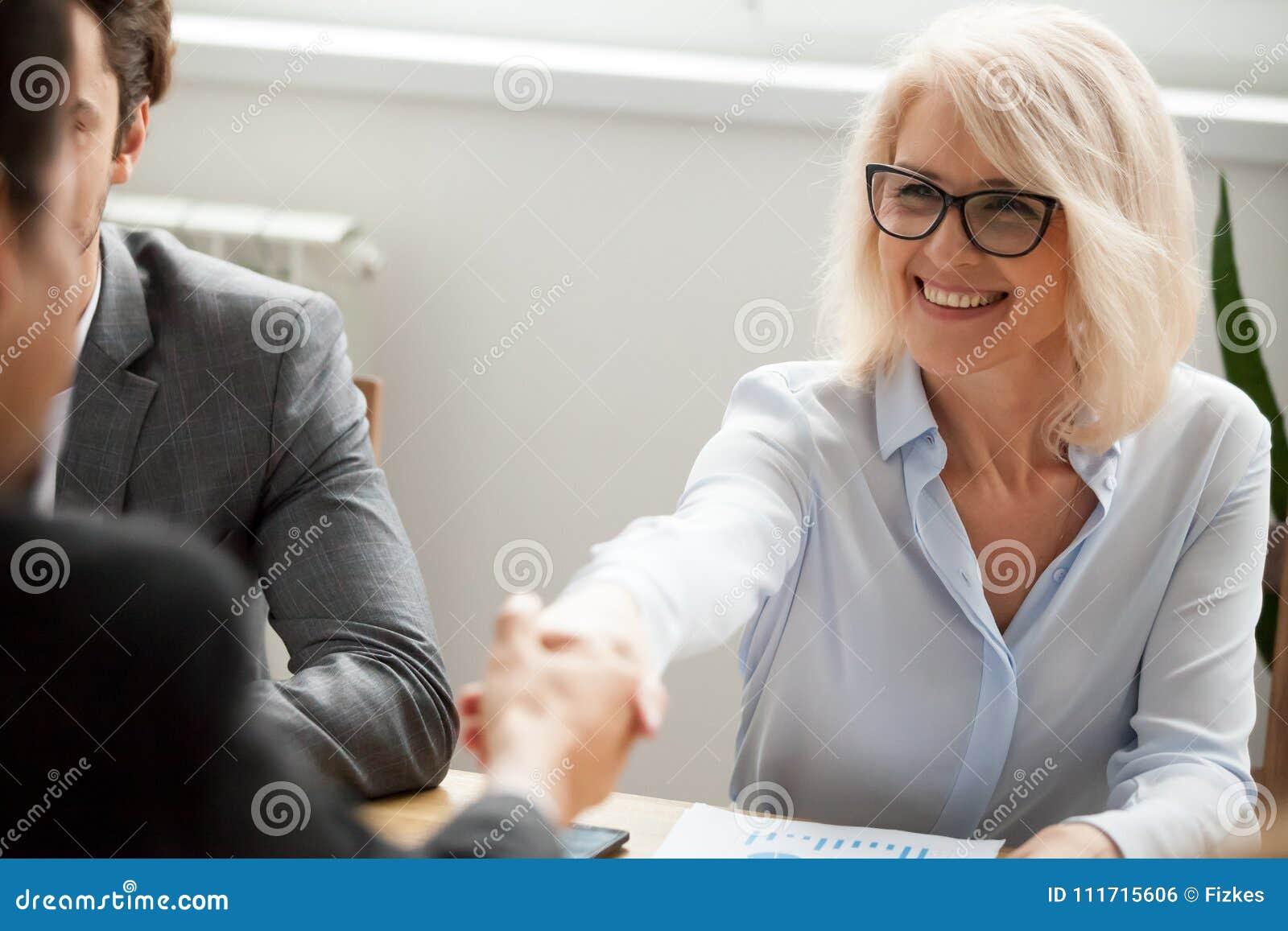 Χαμογελώντας ελκυστικός ώριμος επιχειρηματίας χειραψίας επιχειρηματιών