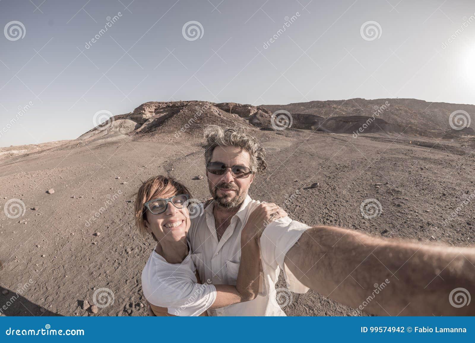 Χαμογελώντας ενήλικο ζεύγος που παίρνει selfie στο εθνικό πάρκο Namib Naukluft, προορισμός ταξιδιού στη Ναμίμπια, Αφρική Fisheye,