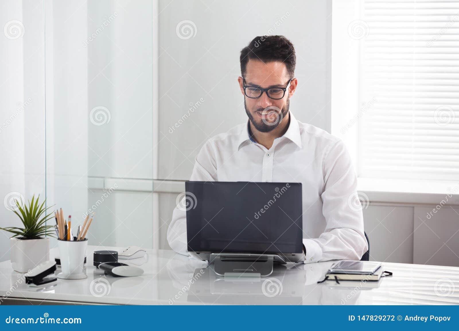 Χαμογελώντας επιχειρηματίας που χρησιμοποιεί το lap-top
