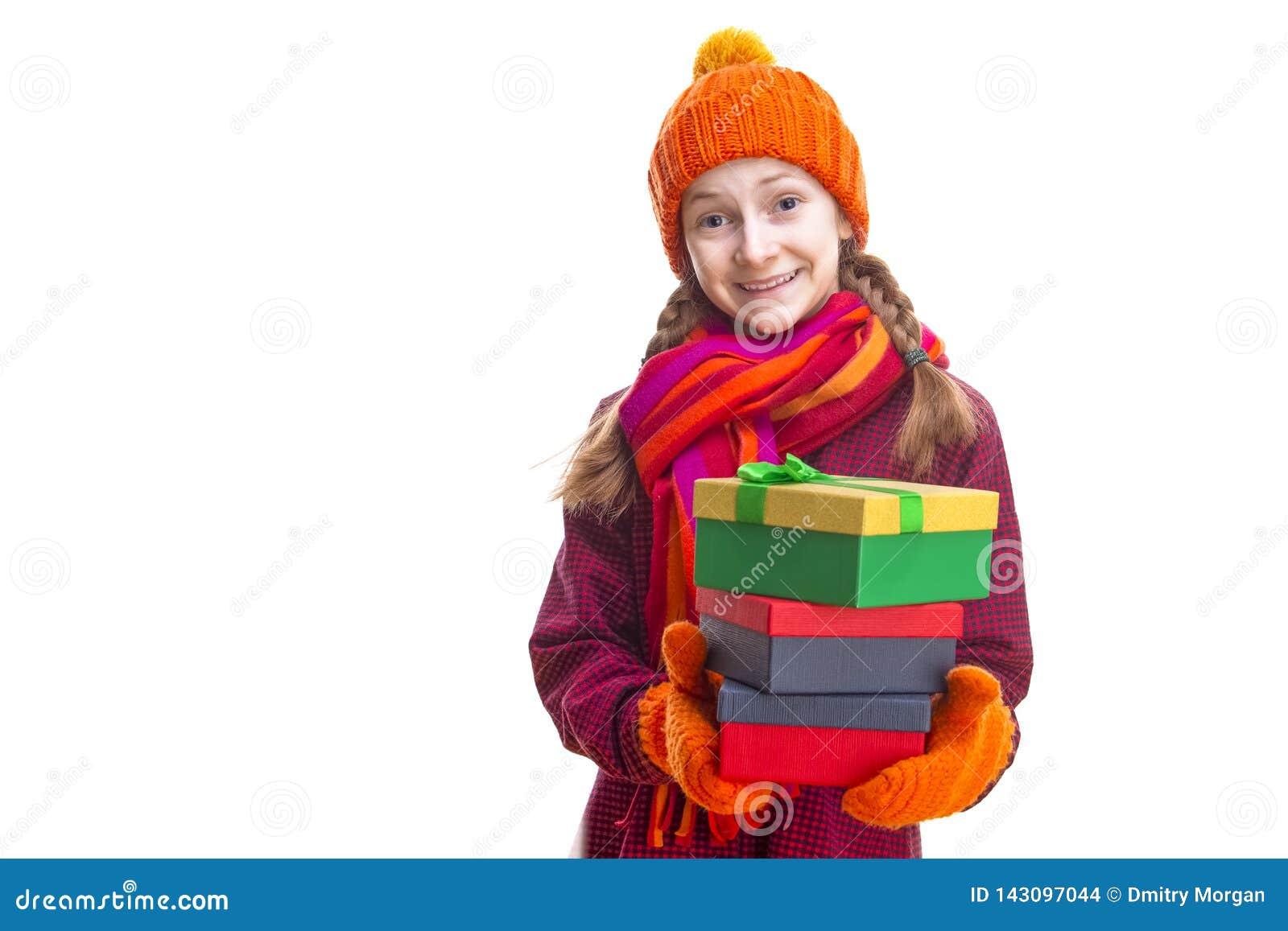 Χαμογελώντας ευτυχές καυκάσιο μικρό κορίτσι σε πορτοκαλιά Beanie, το μαντίλι και τα γάντια με το σωρό ζωηρόχρωμου Giftboxes