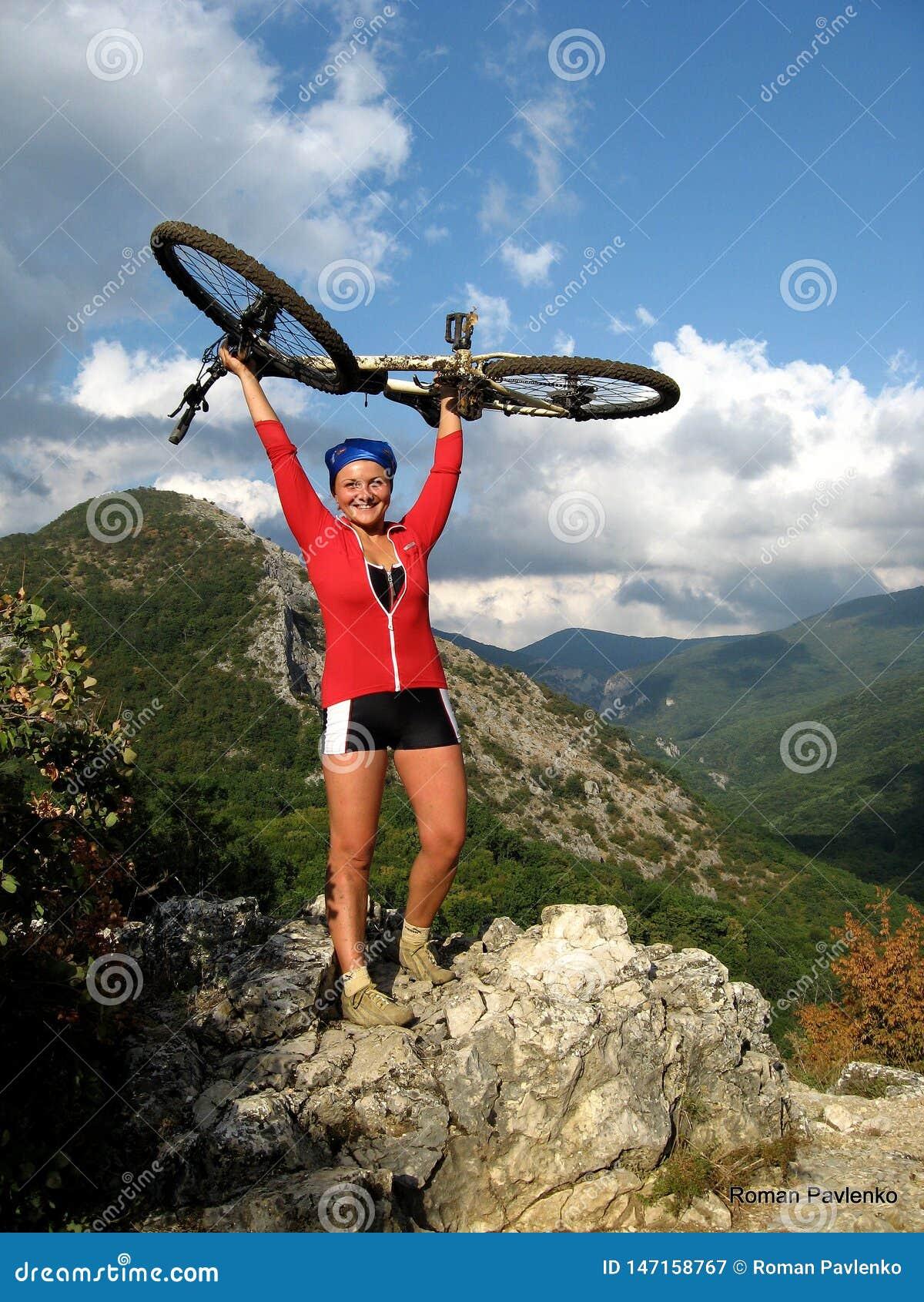 Χαμογελώντας ευτυχές κορίτσι με το ποδήλατο στα βουνά