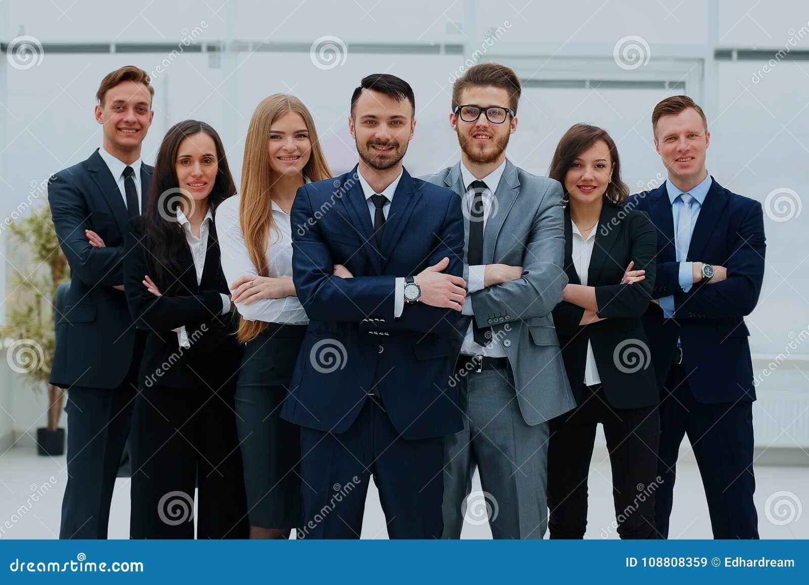 Χαμογελώντας και βέβαια επιχειρησιακή ομάδα που στέκεται μπροστά από ένα φωτεινό παράθυρο