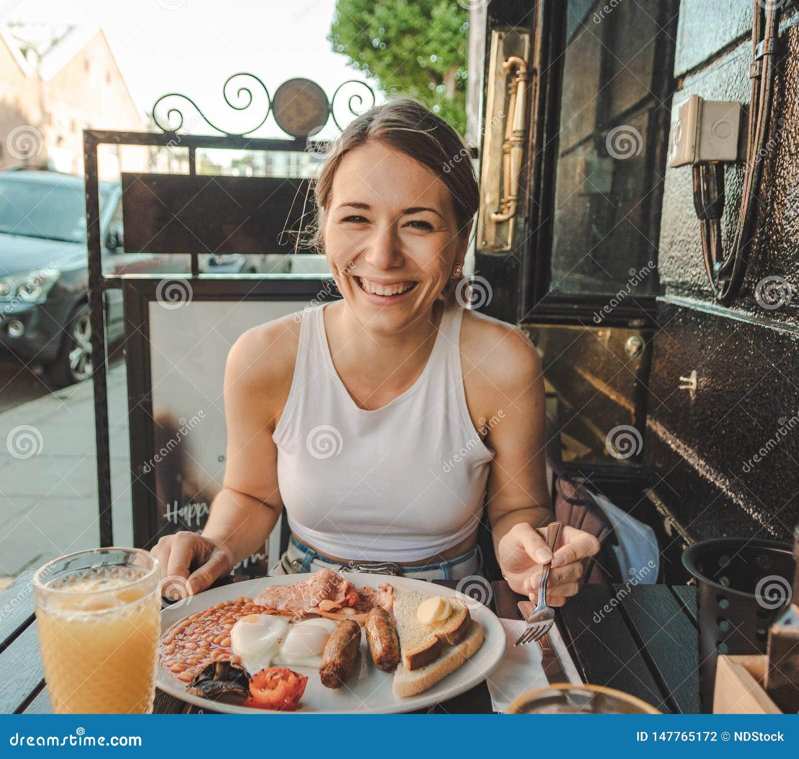 Χαμογελώντας νέα γυναίκα που τρώει ένα αγγλικό πρόγευμα