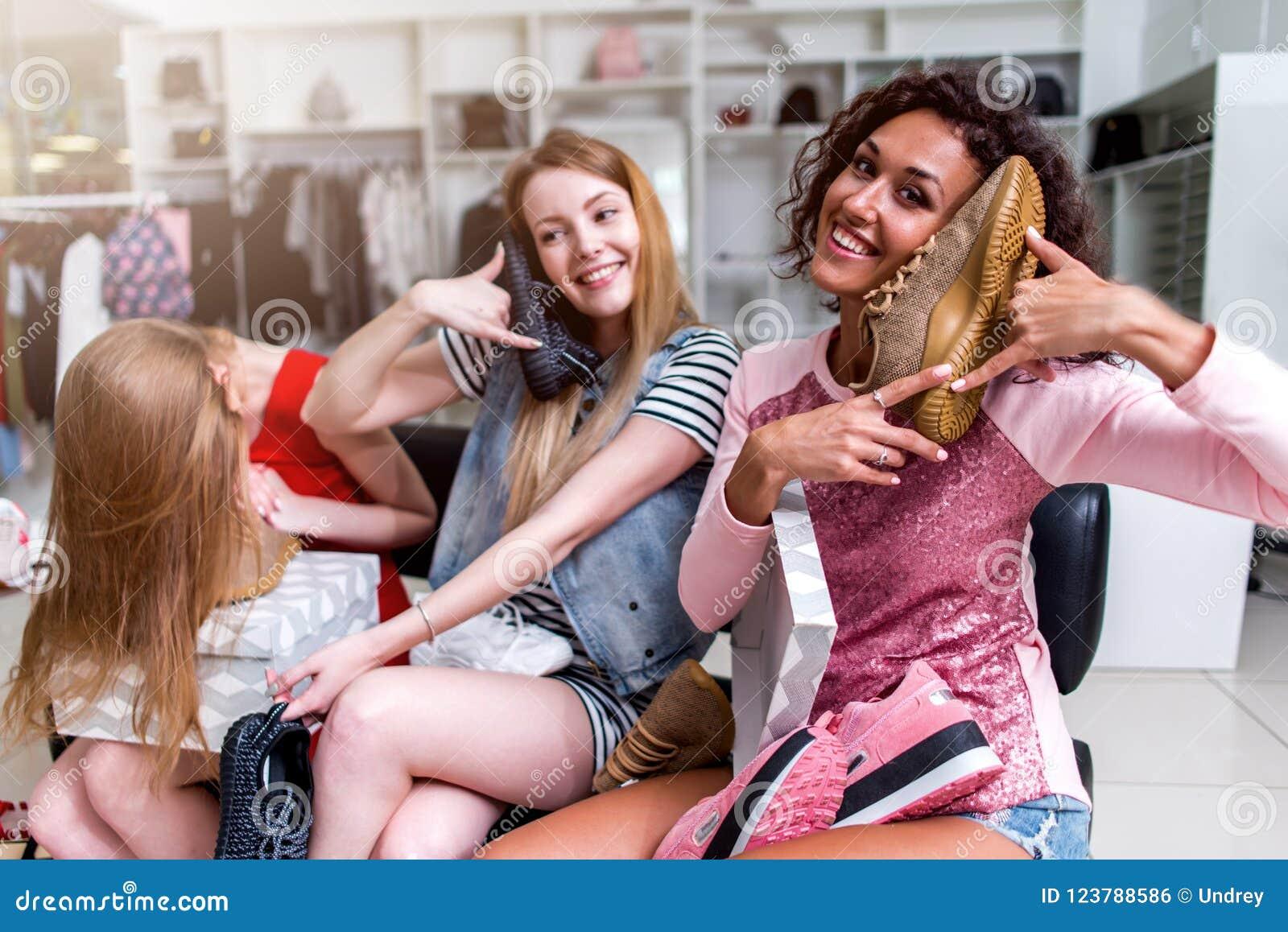 Χαμογελώντας νέες γυναίκες που κάθονται σε ένα womenswear παιχνίδι καταστημάτων με τα νέα υποδήματα που χρησιμοποιούν τα παπούτσι