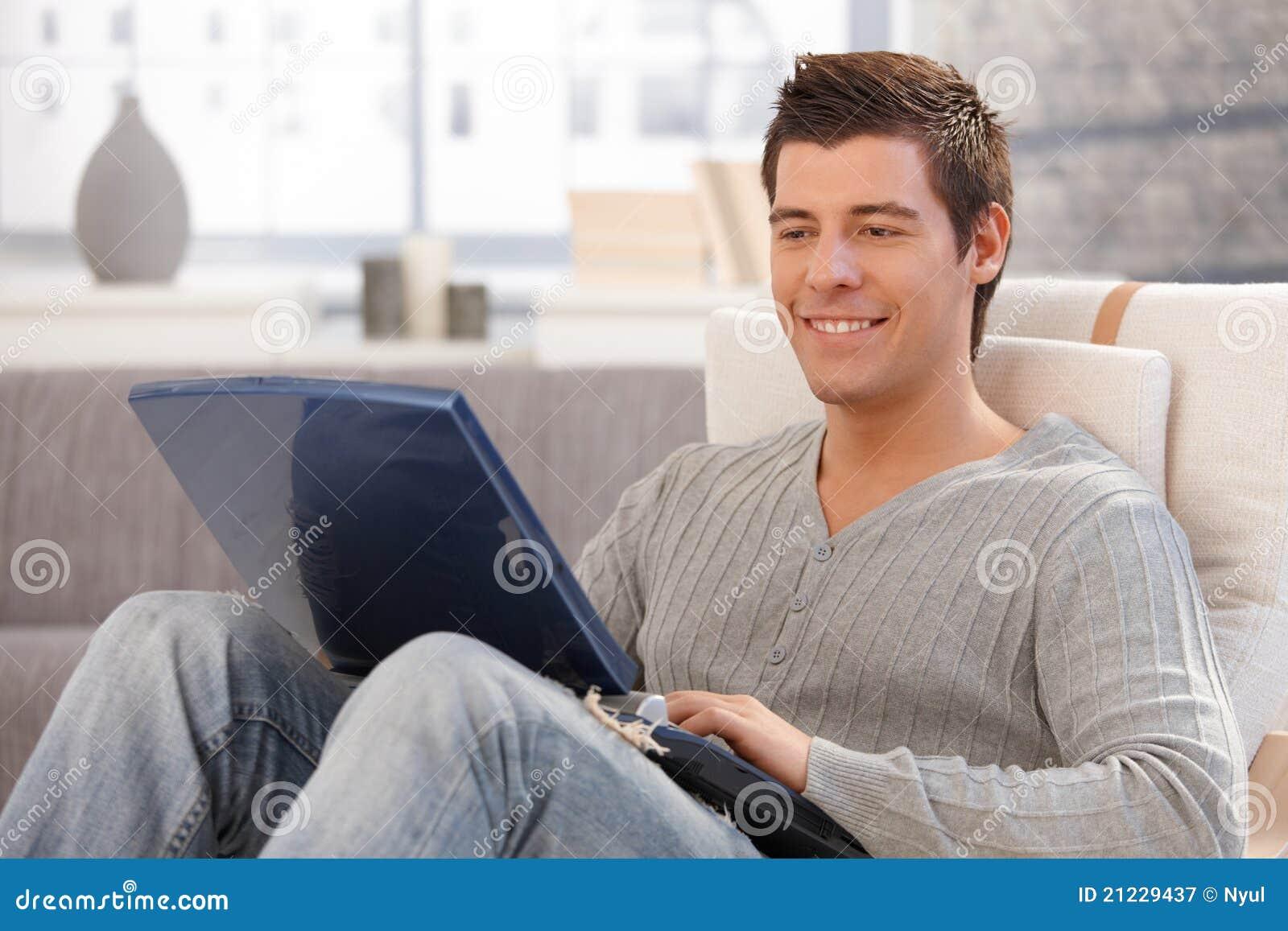 Χαμογελώντας νεαρός άνδρας που χρησιμοποιεί τον υπολογιστή στην πολυθρόνα