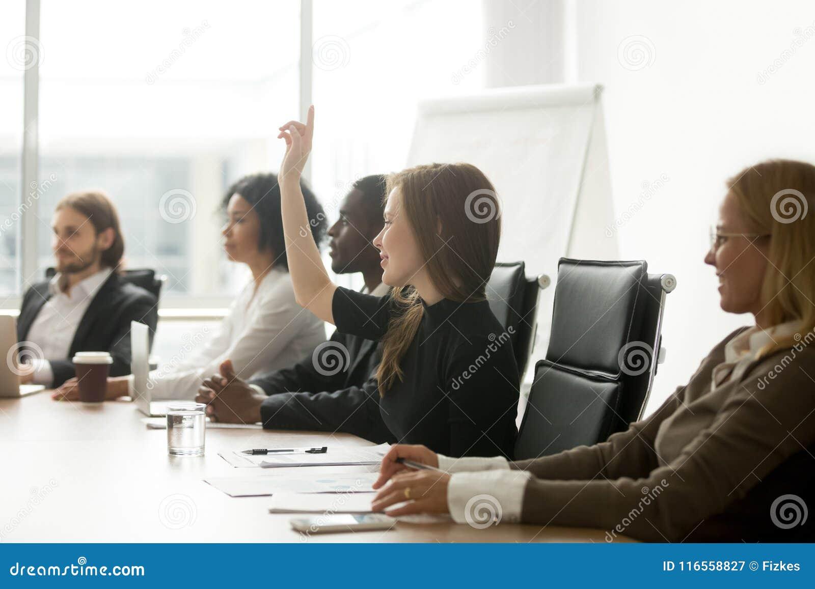 Χαμογελώντας περίεργη επιχειρηματίας που αυξάνει το χέρι στο voti συνεδρίασης της ομάδας