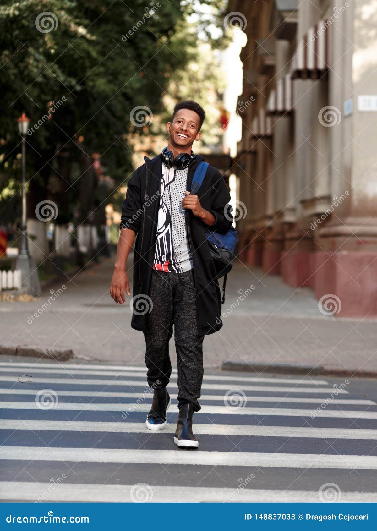 Χαμογελώντας σπουδαστής στα περιστασιακά ενδύματα που ξυπνούν έξω στη διάβαση πεζών, που εξετάζει τη κάμερα, που απομονώνεται σε