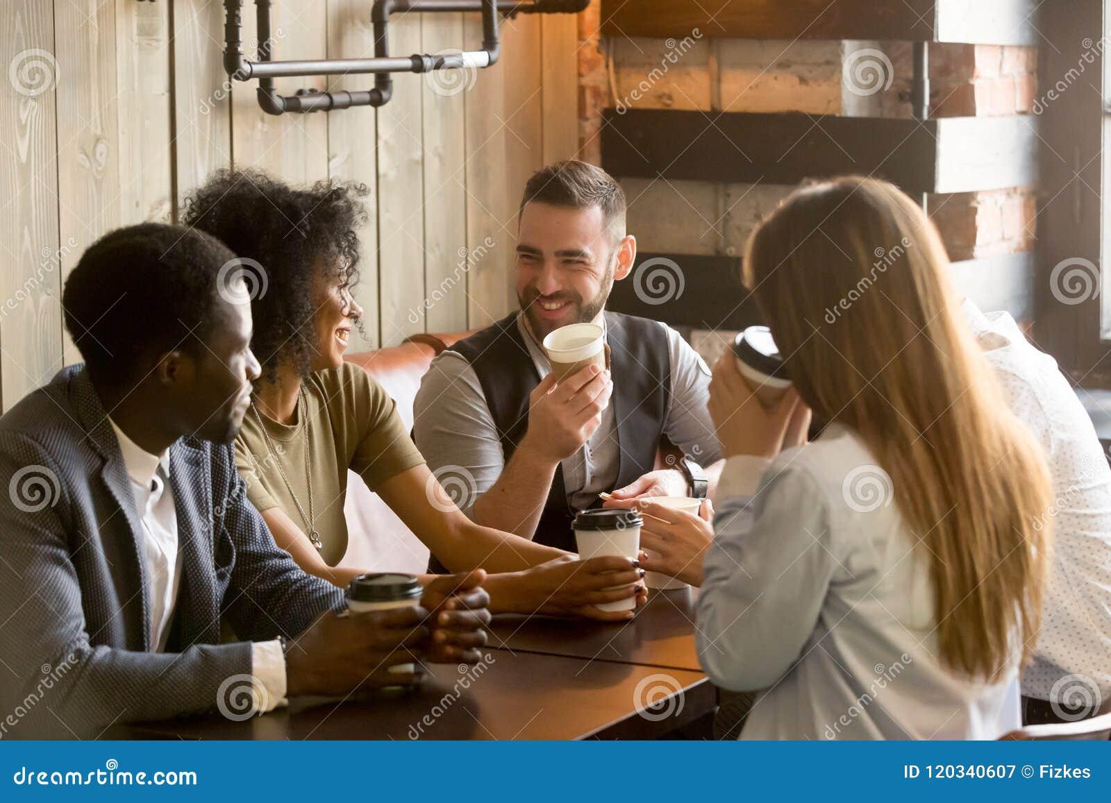 Χαμογελώντας φίλοι που απολαμβάνουν το χρόνο μαζί που έχει τον καφέ στον καφέ