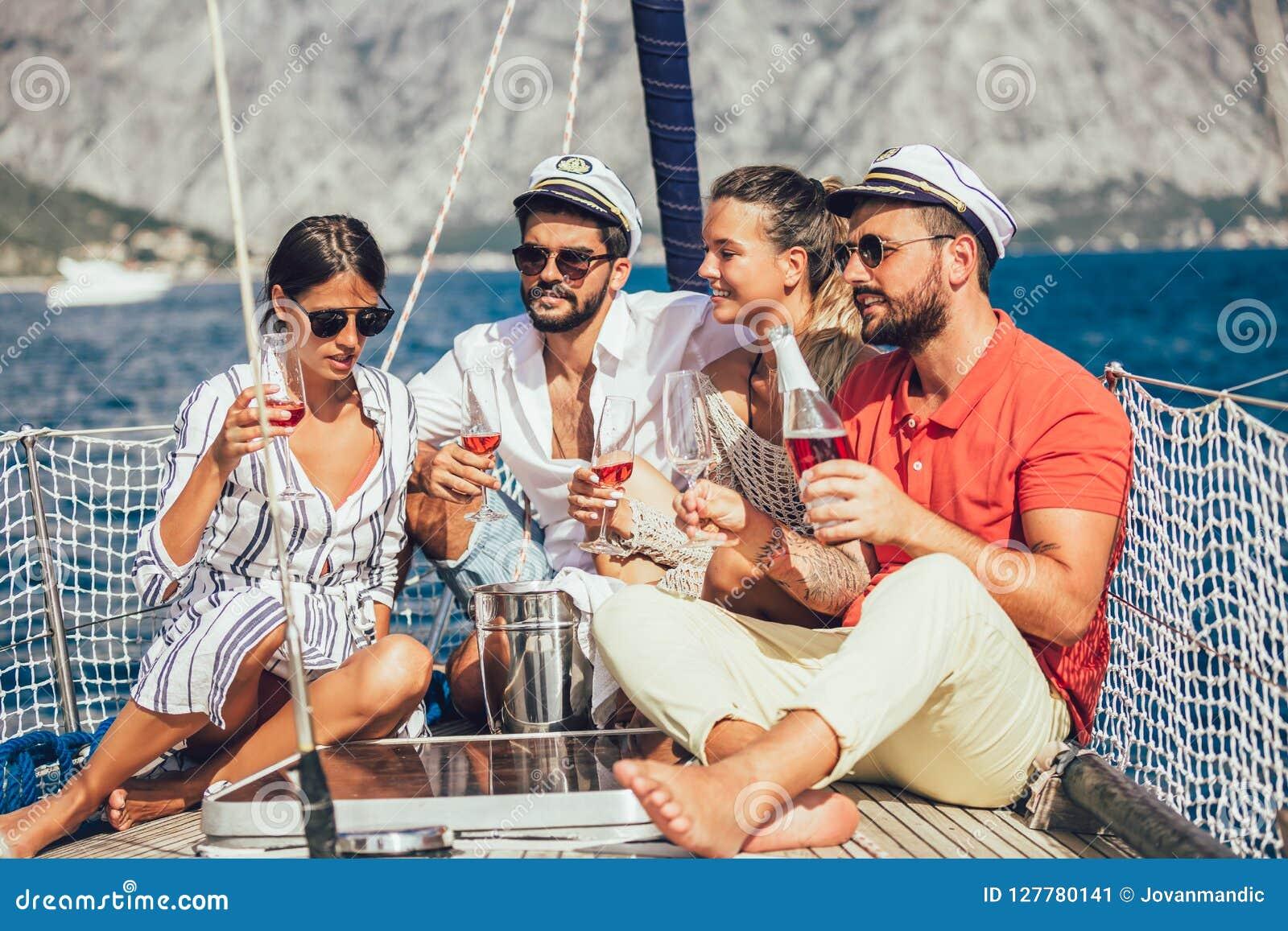 Χαμογελώντας φίλοι που κάθονται sailboat στη γέφυρα και την κατοχή της διασκέδασης