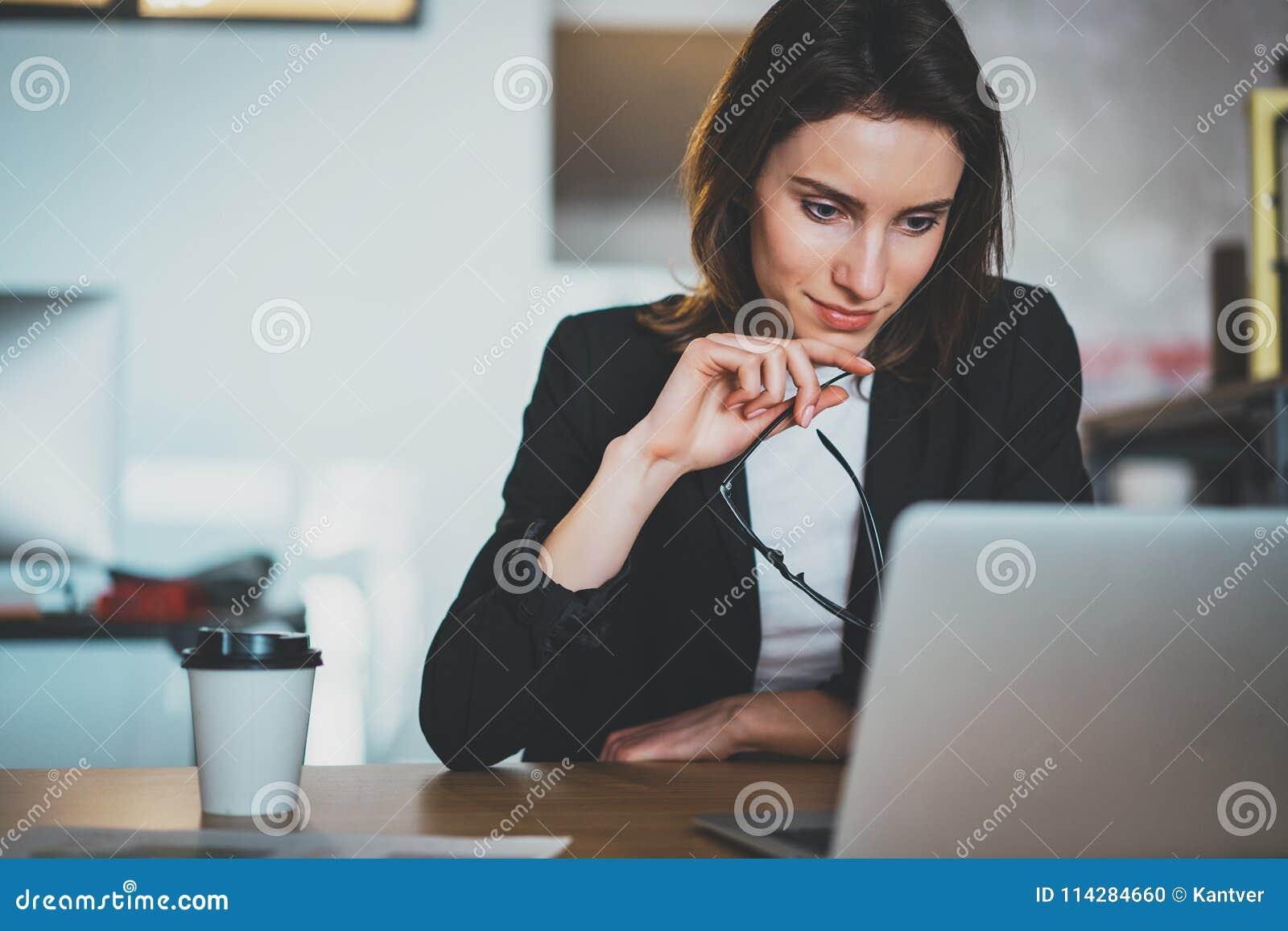 Χαμογελώντας όμορφη επιχειρηματίας που χρησιμοποιεί το φορητό προσωπικό υπολογιστή στο σύγχρονο γραφείο ανασκόπηση που θολώνεται