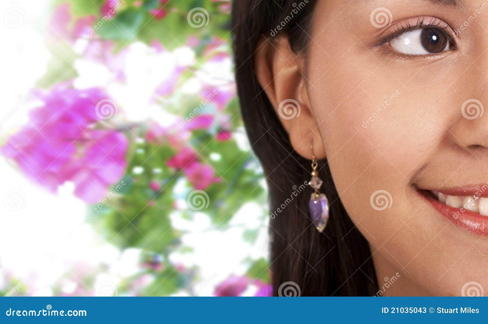Χαμογελώντας όμορφο κορίτσι με την ανασκόπηση λουλουδιών