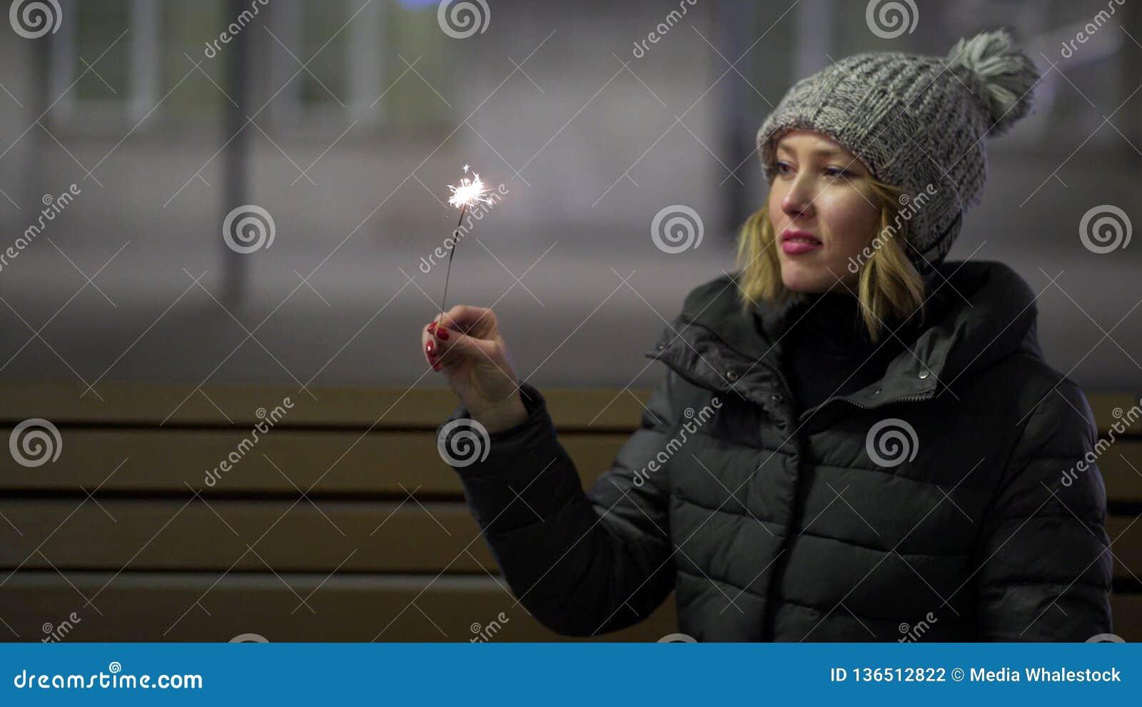 Χαμογελώντας, όμορφο κορίτσι στο πλεκτό καπέλο και κάτω σακάκι στην οδό τη νύχτα με το sparkler, που γιορτάζει το νέο έτος, εύθυμ