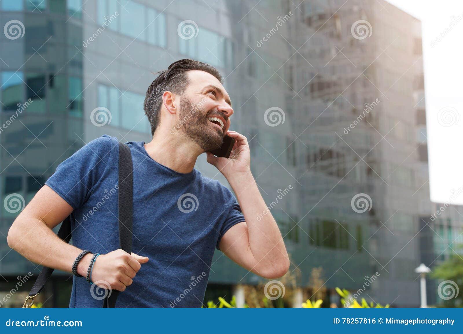 Χαμογελώντας άτομο που μιλά στο κινητό τηλέφωνο υπαίθρια