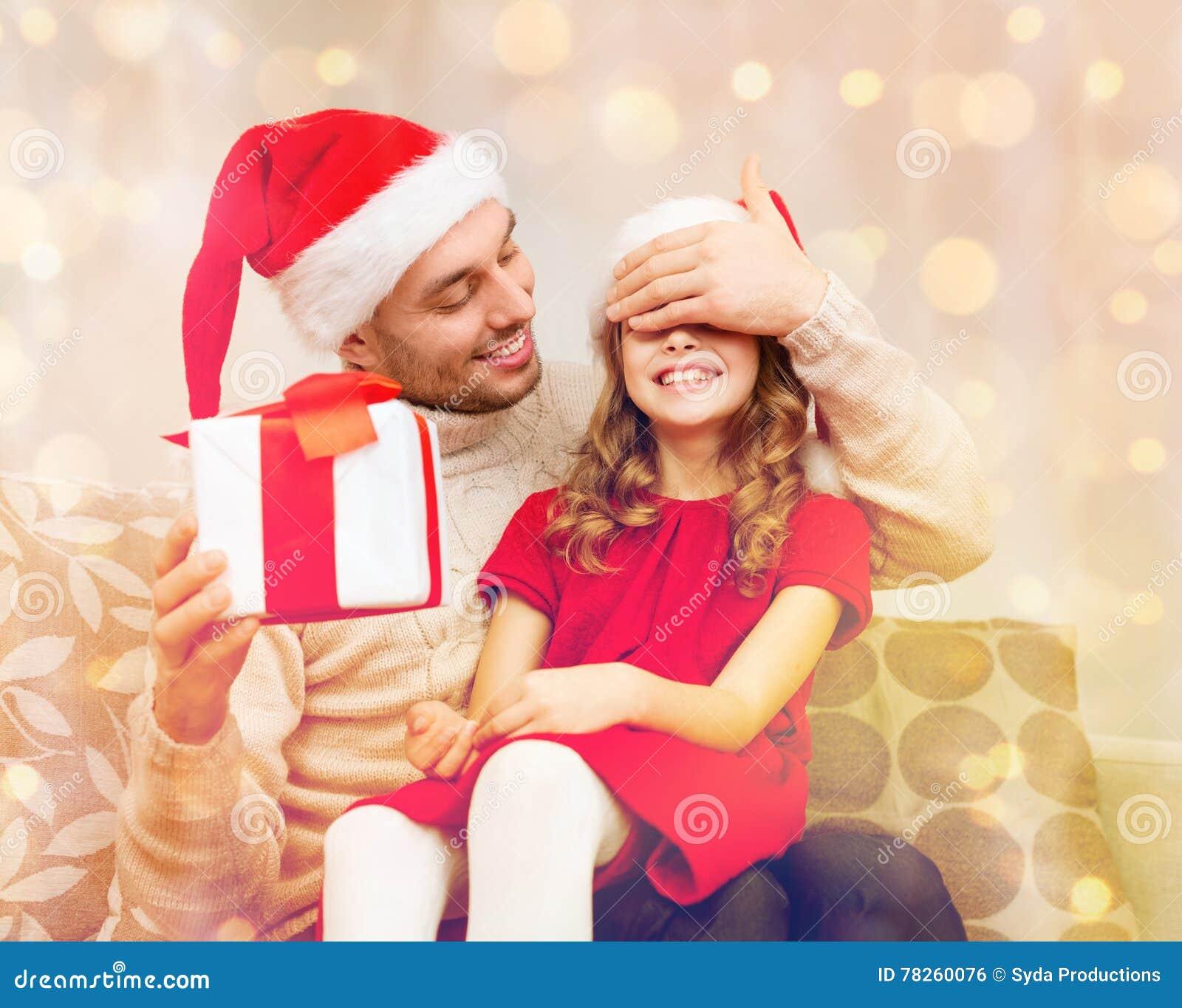 Χαμογελώντας αιφνιδιαστική κόρη πατέρων με το κιβώτιο δώρων