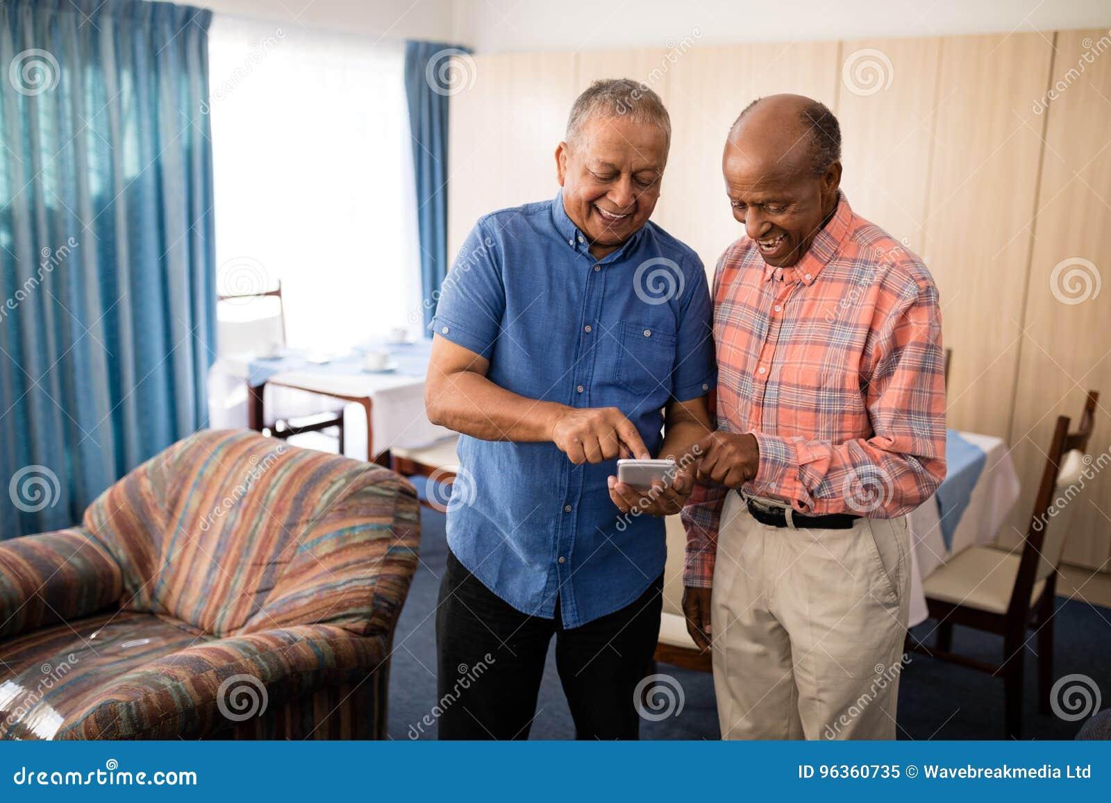 Χαμογελώντας ανώτεροι αρσενικοί φίλοι που χρησιμοποιούν το κινητό τηλέφωνο