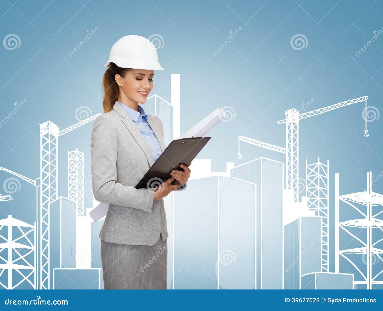 Χαμογελώντας αρχιτέκτονας στο άσπρο κράνος με τα σχεδιαγράμματα