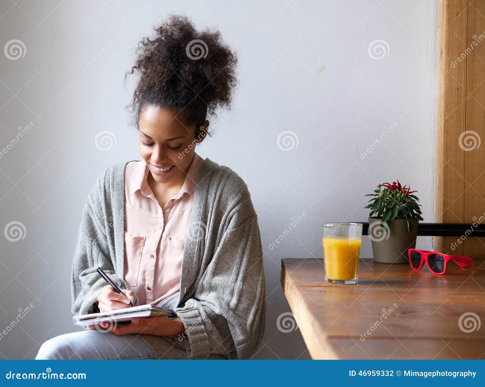 Χαμογελώντας γυναίκα που γράφει στο σημειωματάριο στο σπίτι