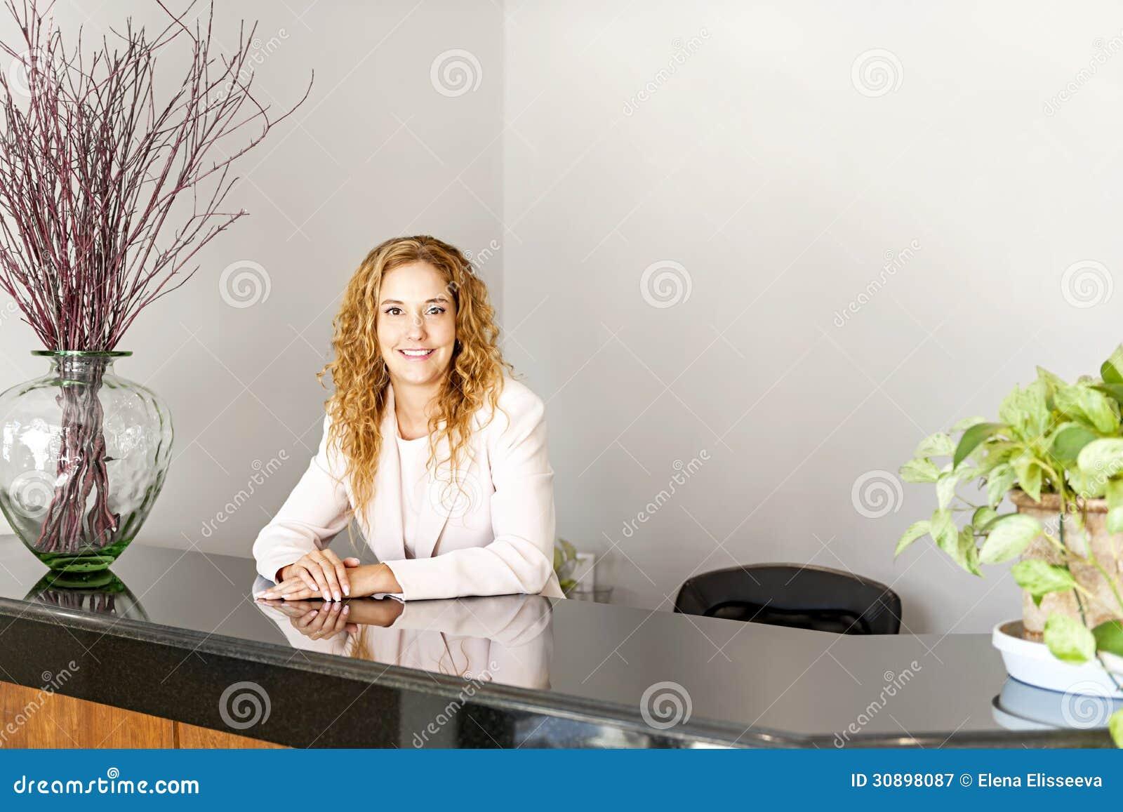 Χαμογελώντας γυναίκα στην υποδοχή γραφείων