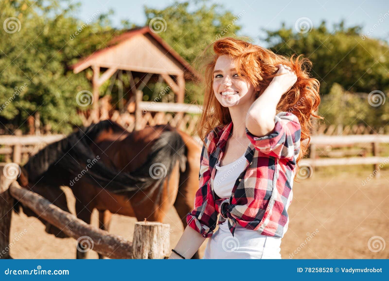 Χαμογελώντας γυναίκα cowgirl με τη συνεδρίαση αλόγων στο αγρόκτημα