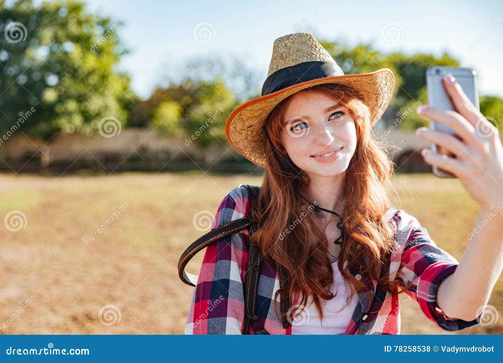 Χαμογελώντας γυναίκα cowgirl που παίρνει selfie με το κινητό τηλέφωνο στο αγρόκτημα