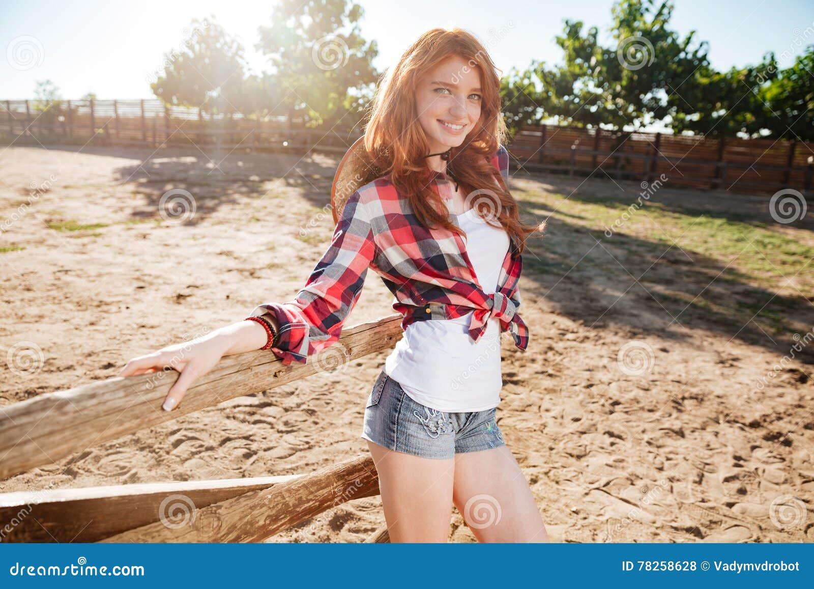 Χαμογελώντας γυναίκα cowgirl που στέκεται στο αγρόκτημα