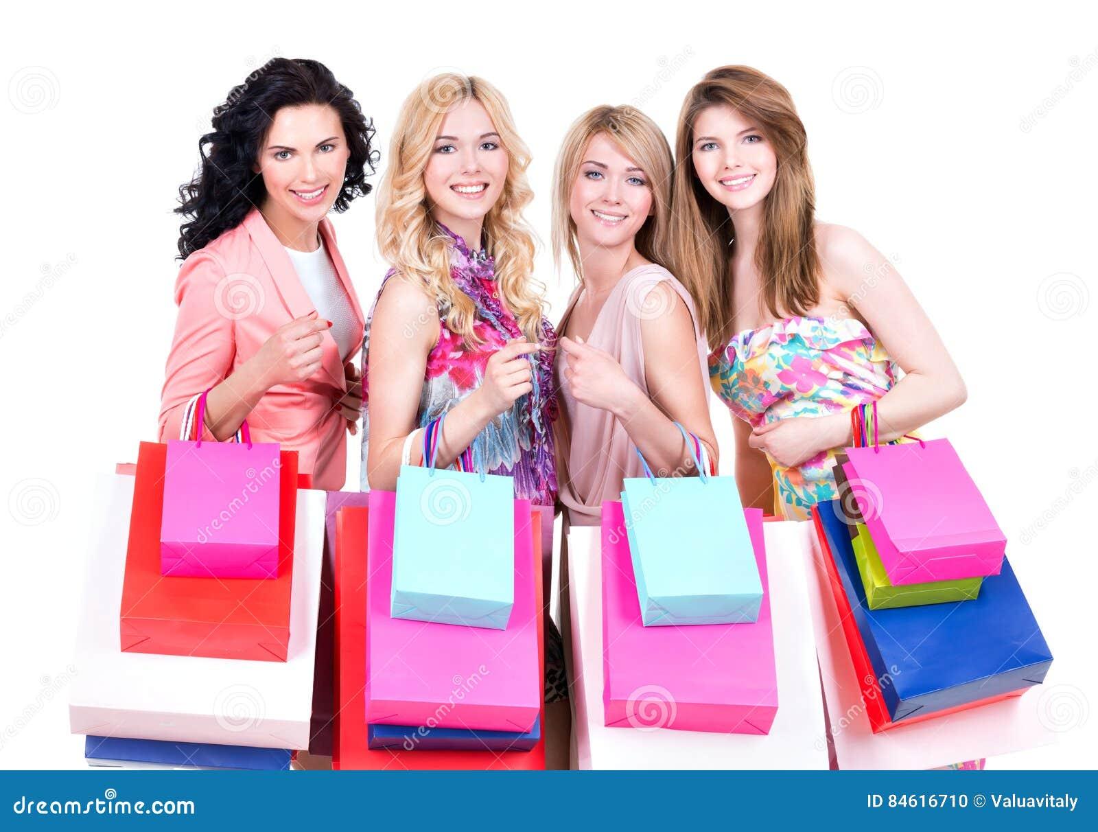 Χαμογελώντας γυναίκες με τις πολύχρωμες τσάντες αγορών