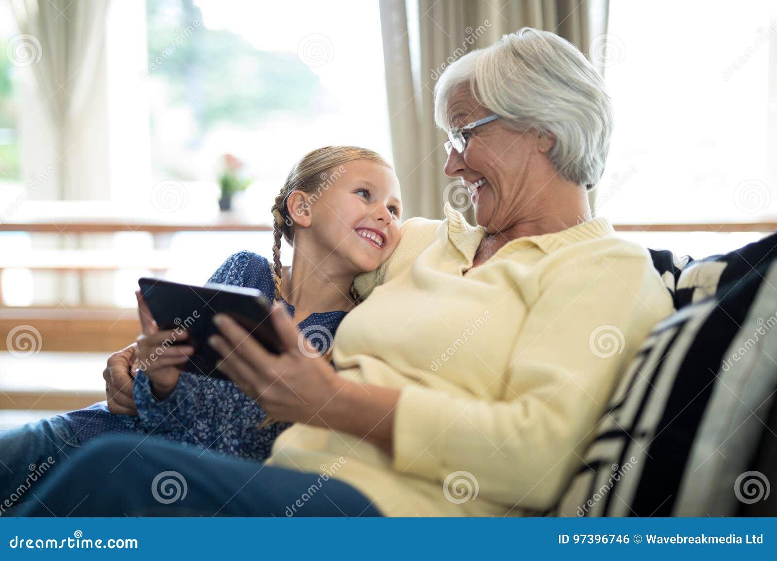 Χαμογελώντας εγγονή και γιαγιά που χρησιμοποιούν την ψηφιακή ταμπλέτα στον καναπέ