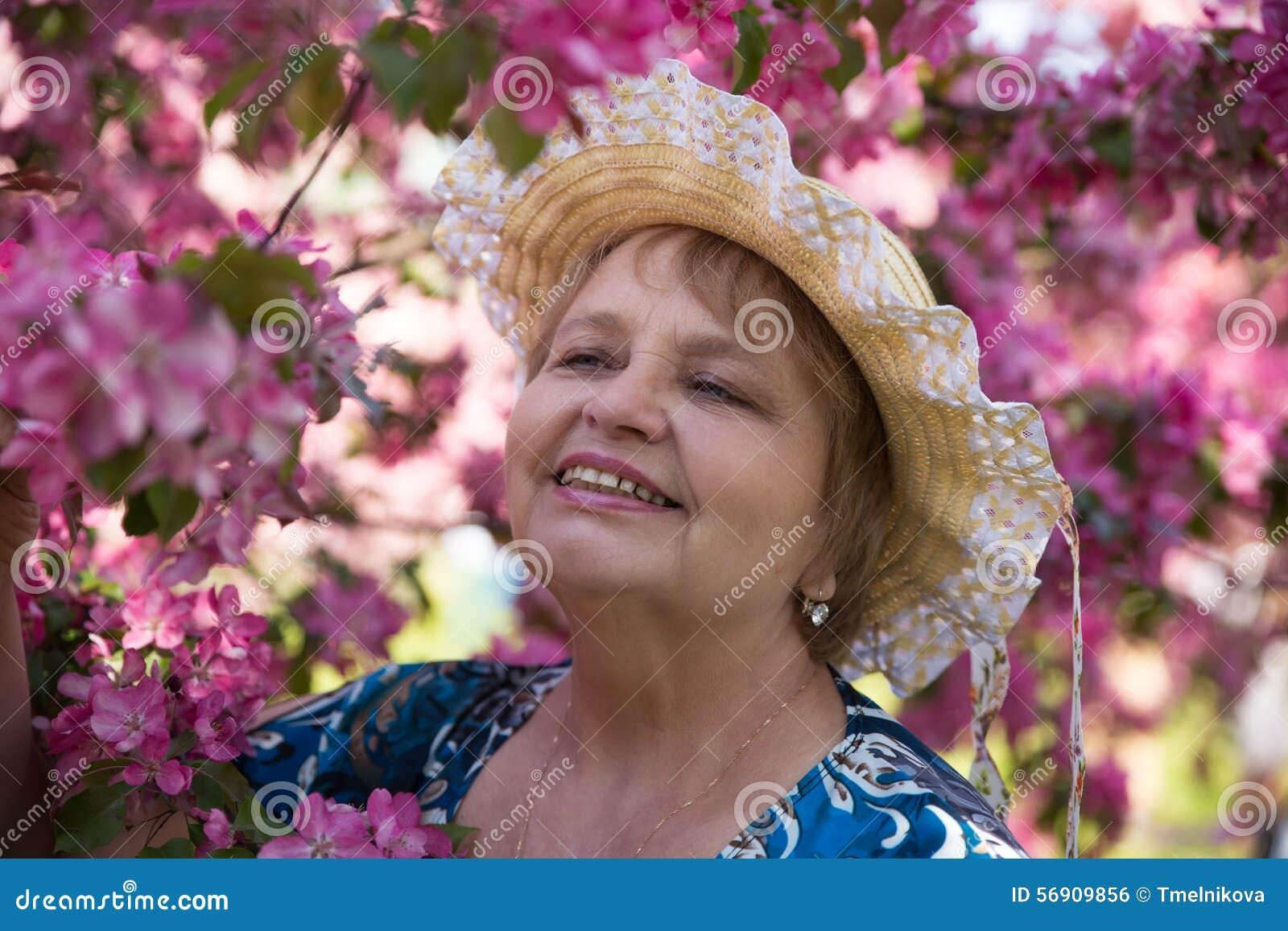 Χαμογελώντας ενήλικη γυναίκα που φορά ένα καπέλο κάτω από το ροζ