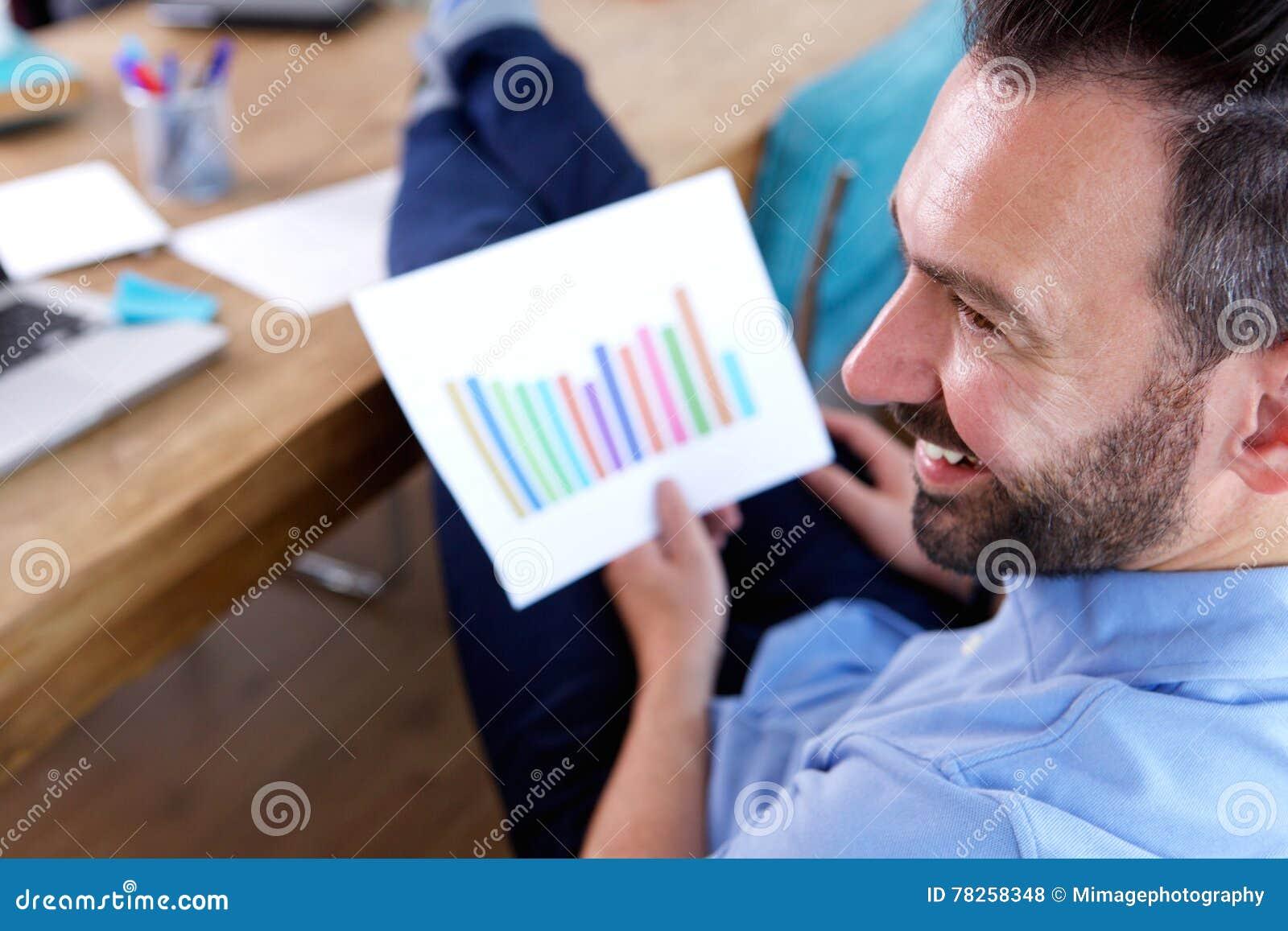 Χαμογελώντας επιχειρησιακό άτομο με τα διαγράμματα στο γραφείο του