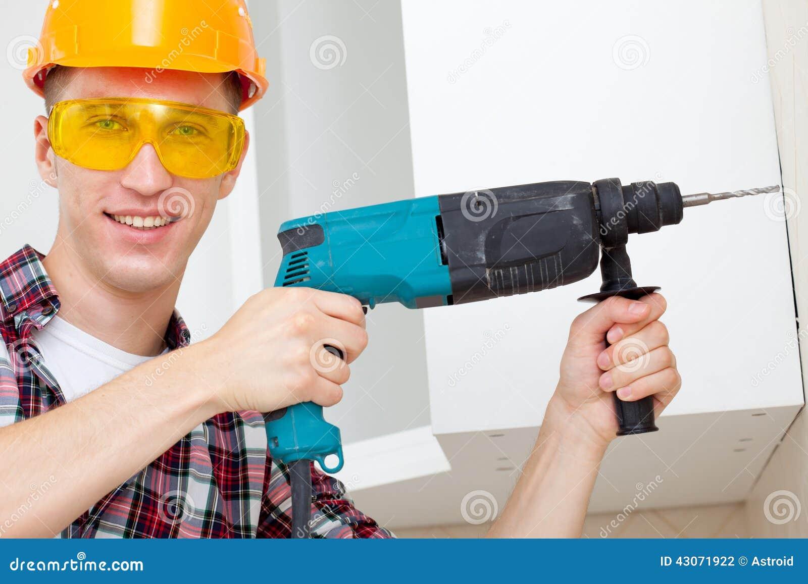 Χαμογελώντας εργαζόμενος με το βράχος-τρυπάνι
