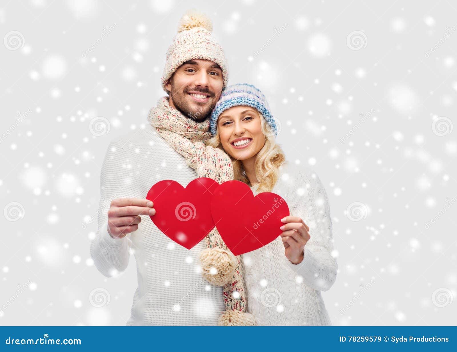 Χαμογελώντας ζεύγος στα χειμερινά ενδύματα με τις κόκκινες καρδιές