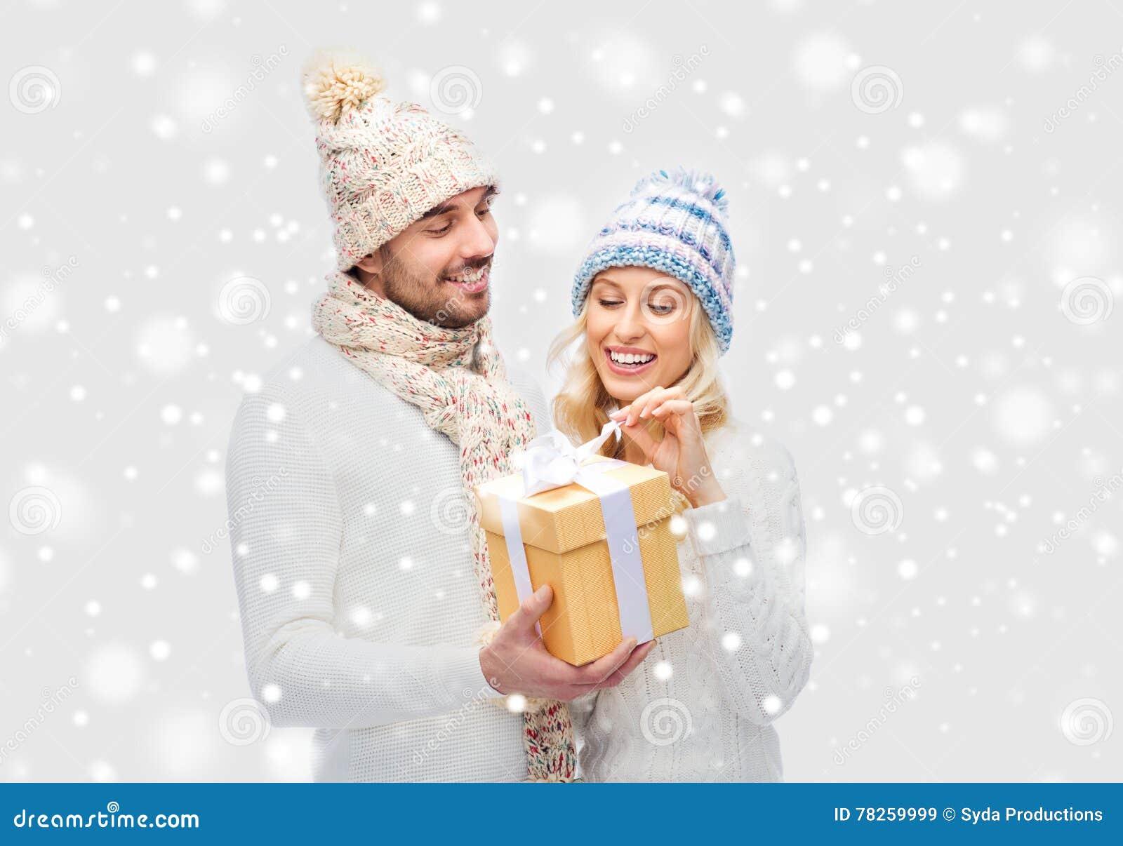 Χαμογελώντας ζεύγος στα χειμερινά ενδύματα με το κιβώτιο δώρων