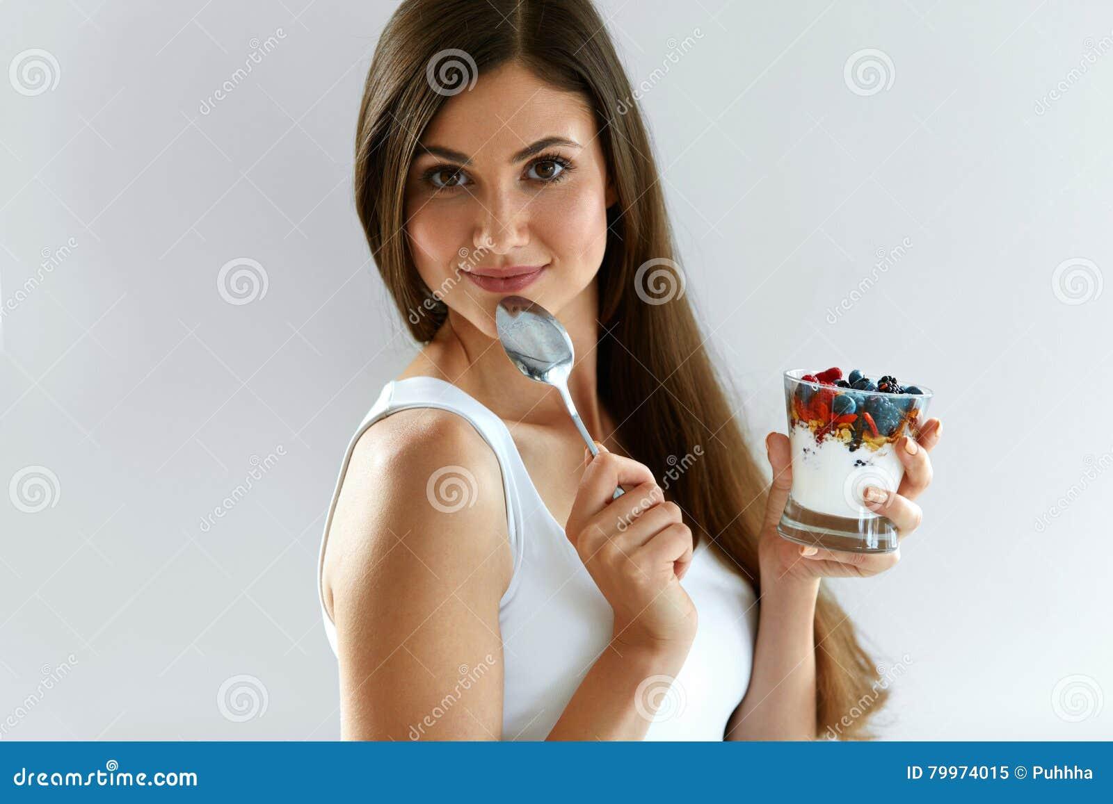 Χαμογελώντας κορίτσι που τρώει το υγιές οργανικό γιαούρτι με τα μούρα και τις βρώμες
