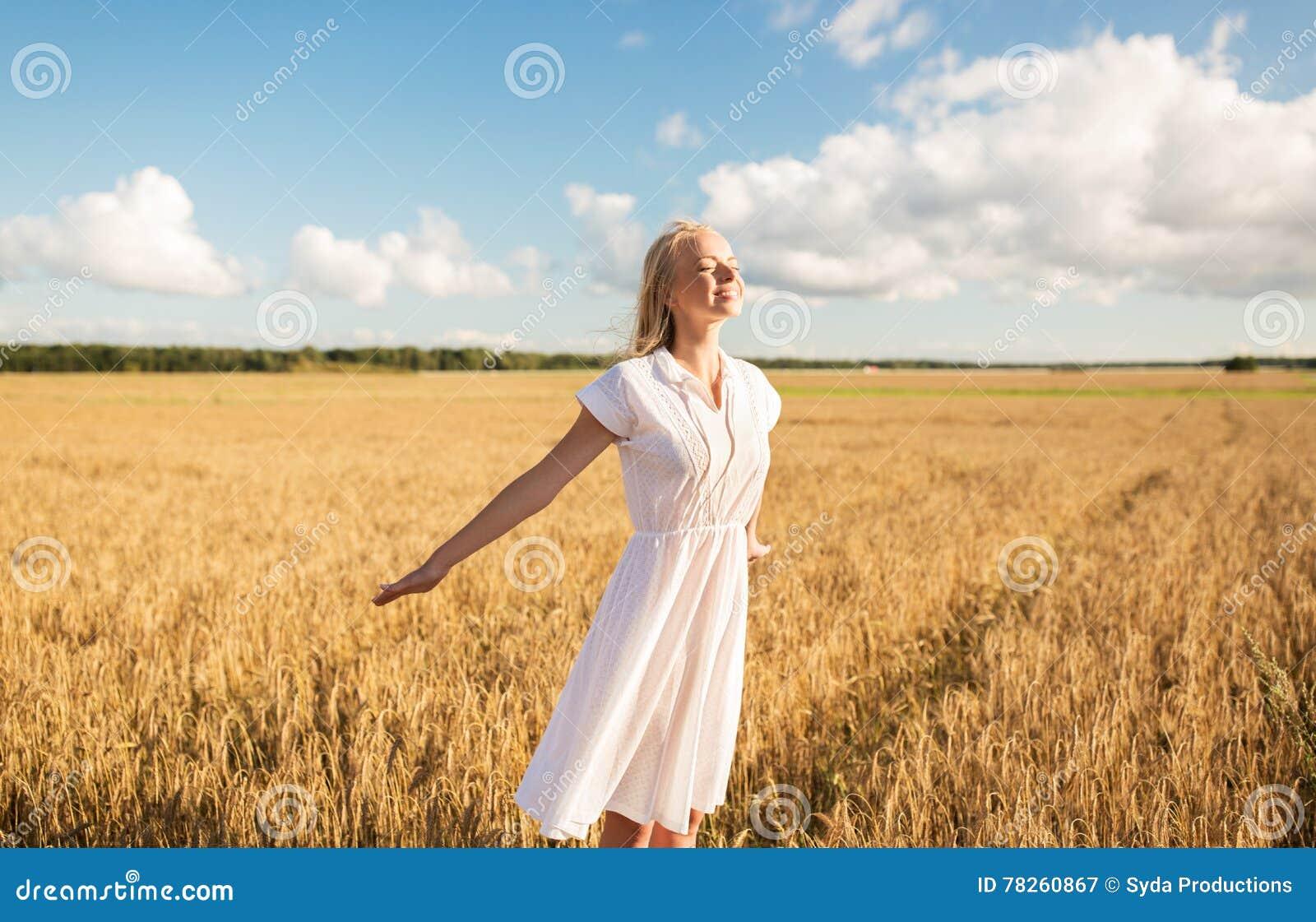Χαμογελώντας νέα γυναίκα στο άσπρο φόρεμα στον τομέα δημητριακών