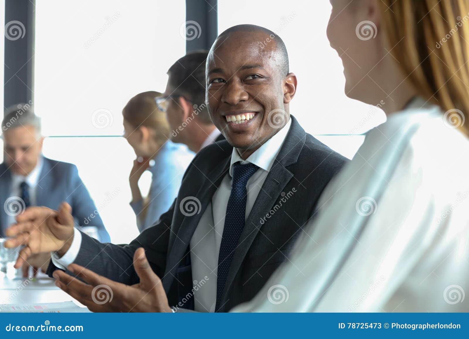 Χαμογελώντας νέος επιχειρηματίας που συζητά με τη γυναίκα συνάδελφος στο δωμάτιο πινάκων