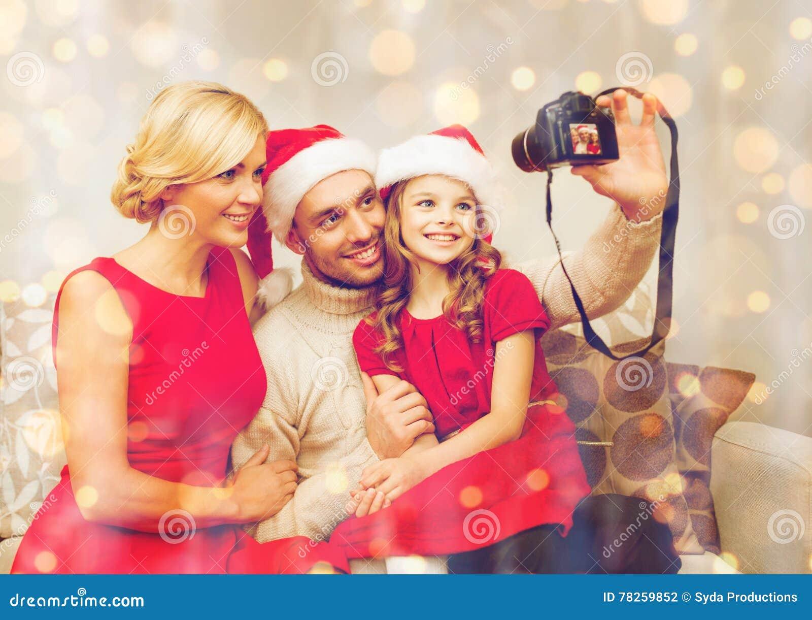 Χαμογελώντας οικογένεια στα καπέλα αρωγών santa που παίρνουν την εικόνα