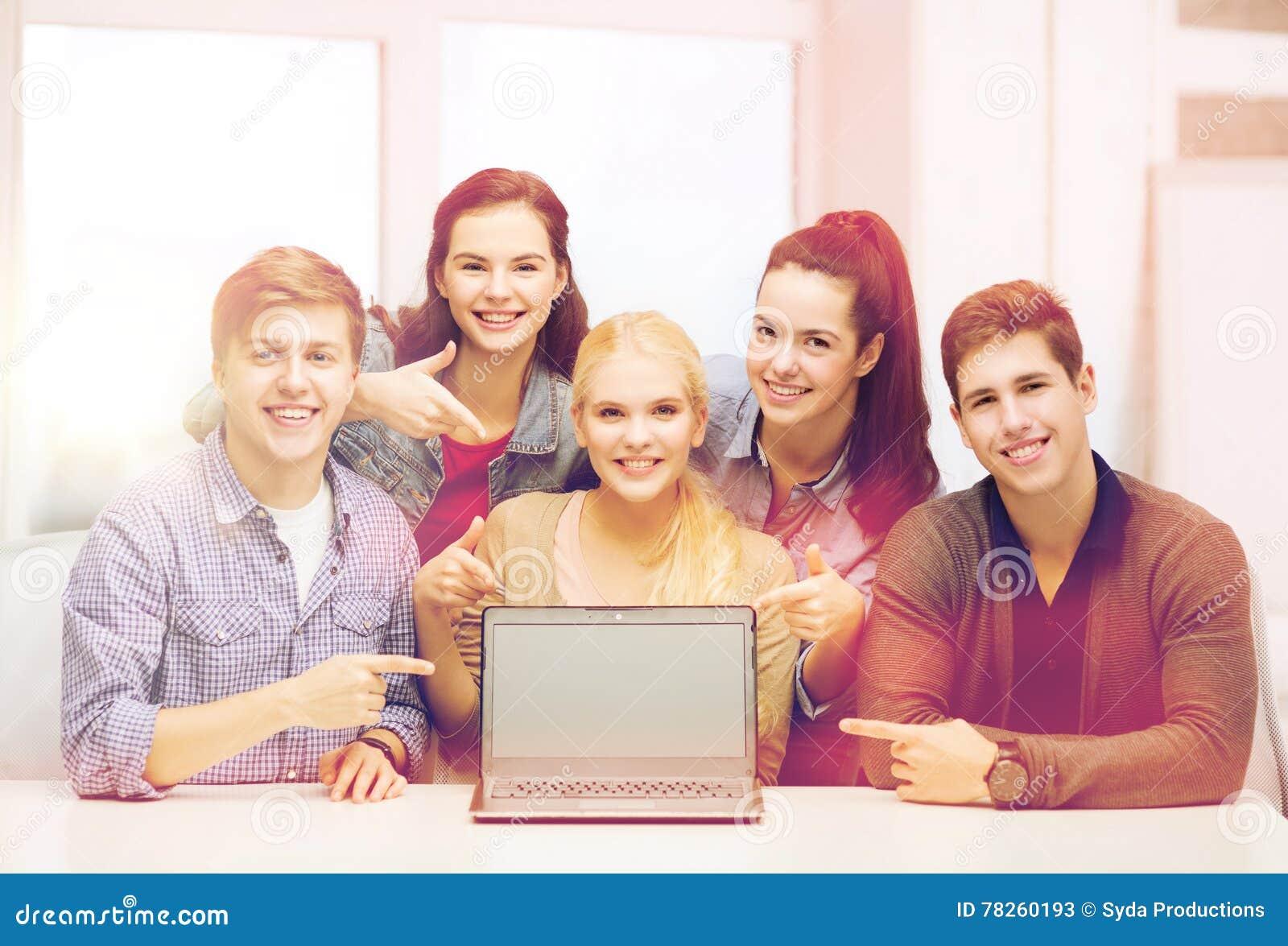Χαμογελώντας σπουδαστές που δείχνουν την κενή οθόνη lapotop