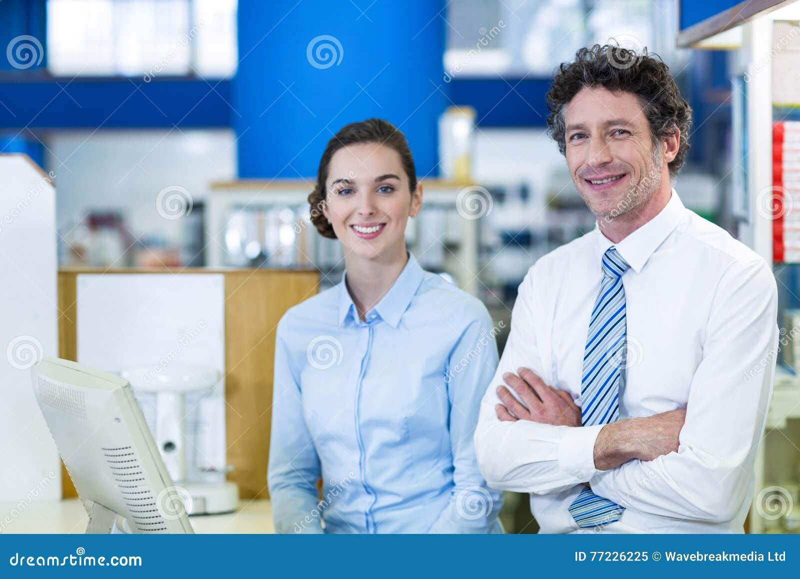 Χαμογελώντας φαρμακοποιοί που στέκονται στο μετρητή στο φαρμακείο
